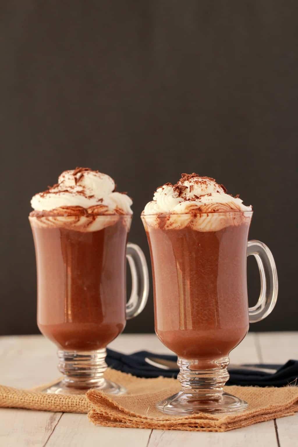 Vegan Hot Chocolate in glass mugs standing against a dark background.