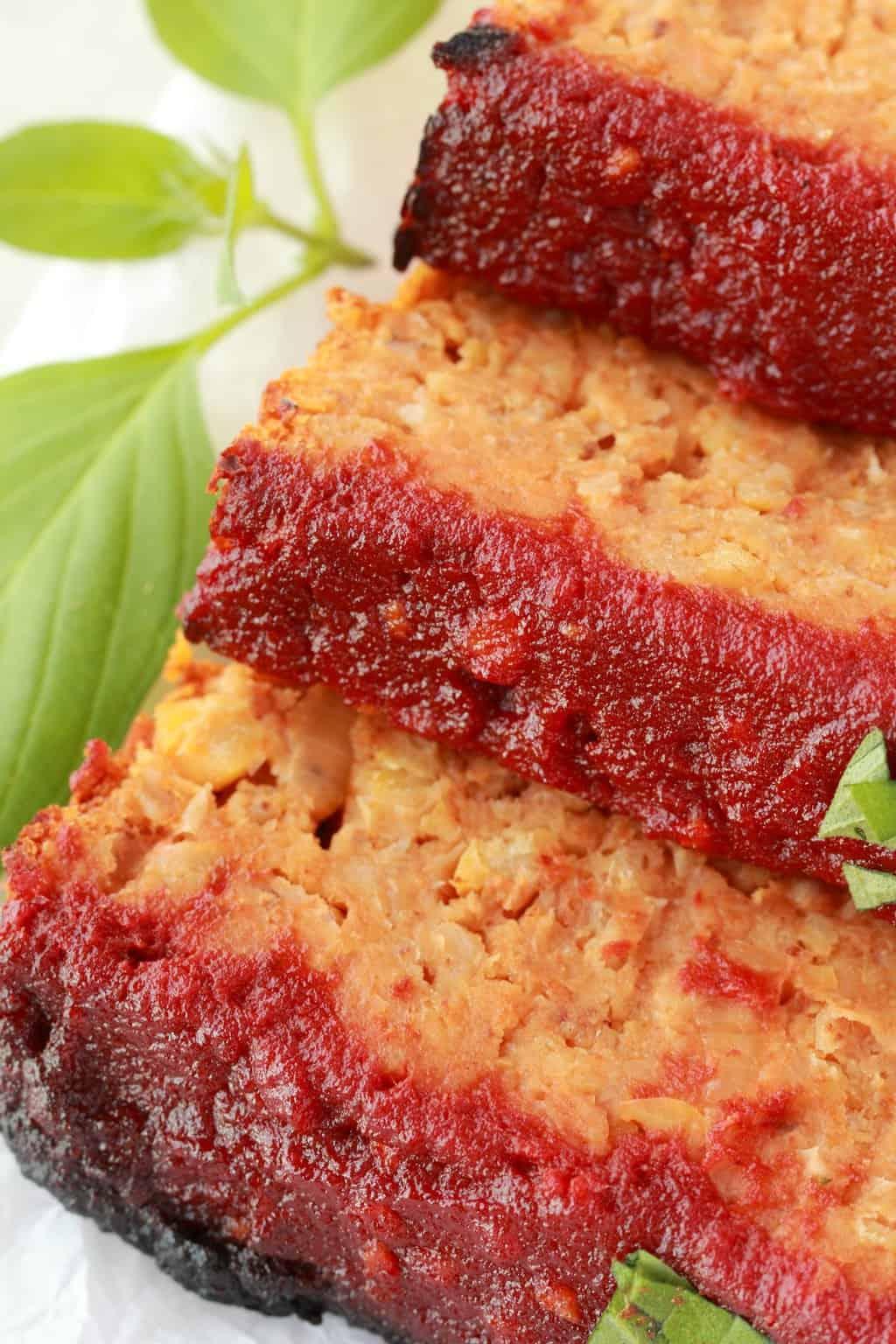 Vegan Meatloaf sliced, close up, fresh basil in the background.