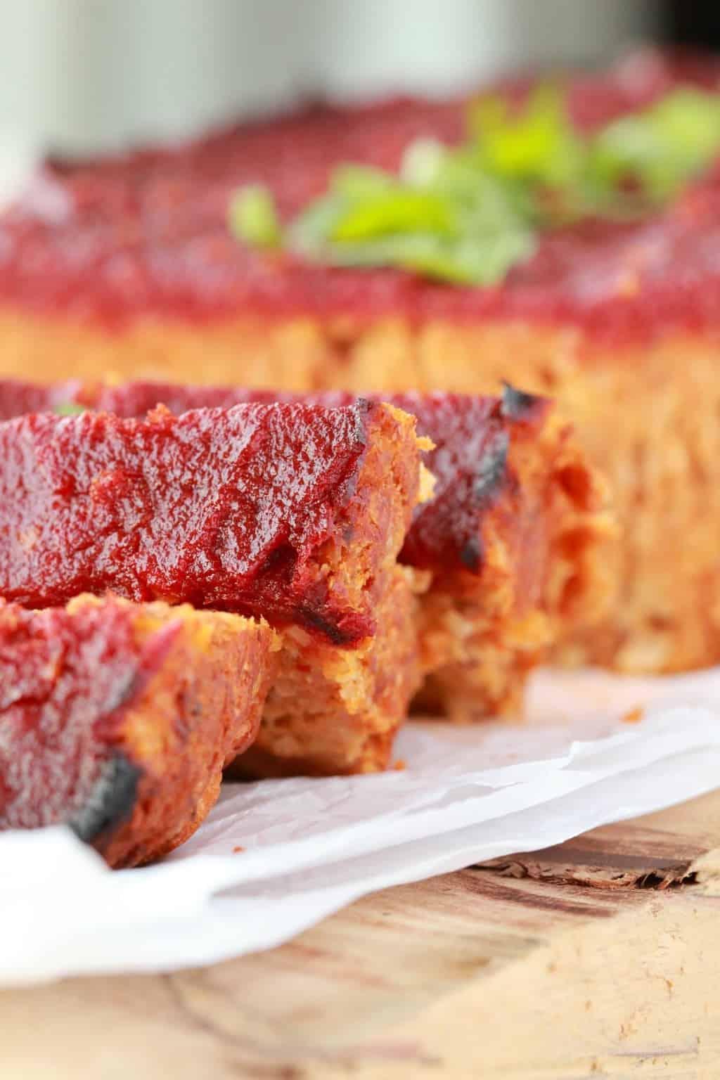 Sliced vegan meatloaf with fresh basil on top.