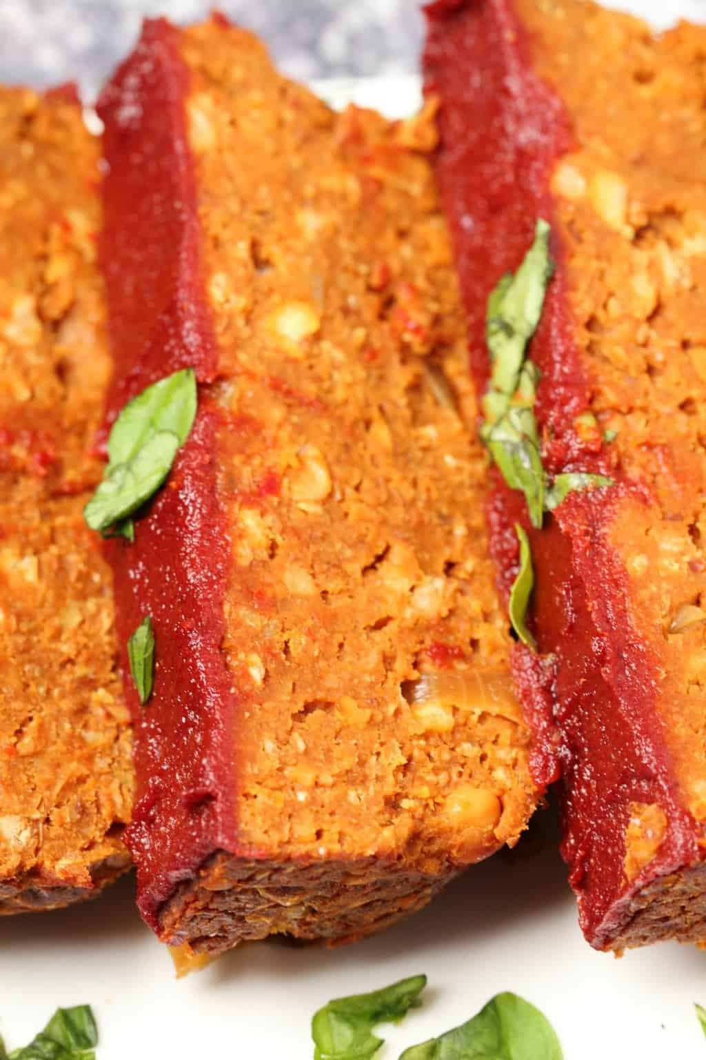 Vegan meatloaf slices on a white plate.