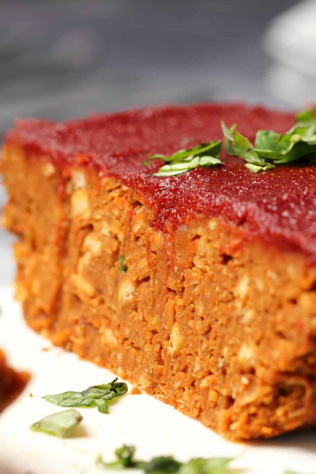 Vegan meatloaf topped with a tomato glaze and fresh basil on a white plate.