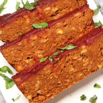 Slices of vegan meatloaf on a white plate.