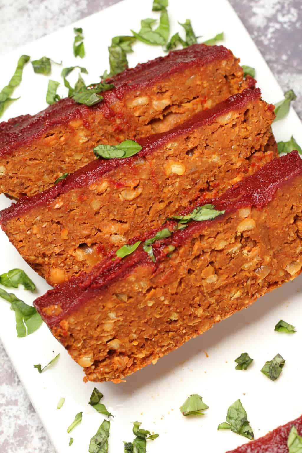Vegan meatloaf slices on a white plate.