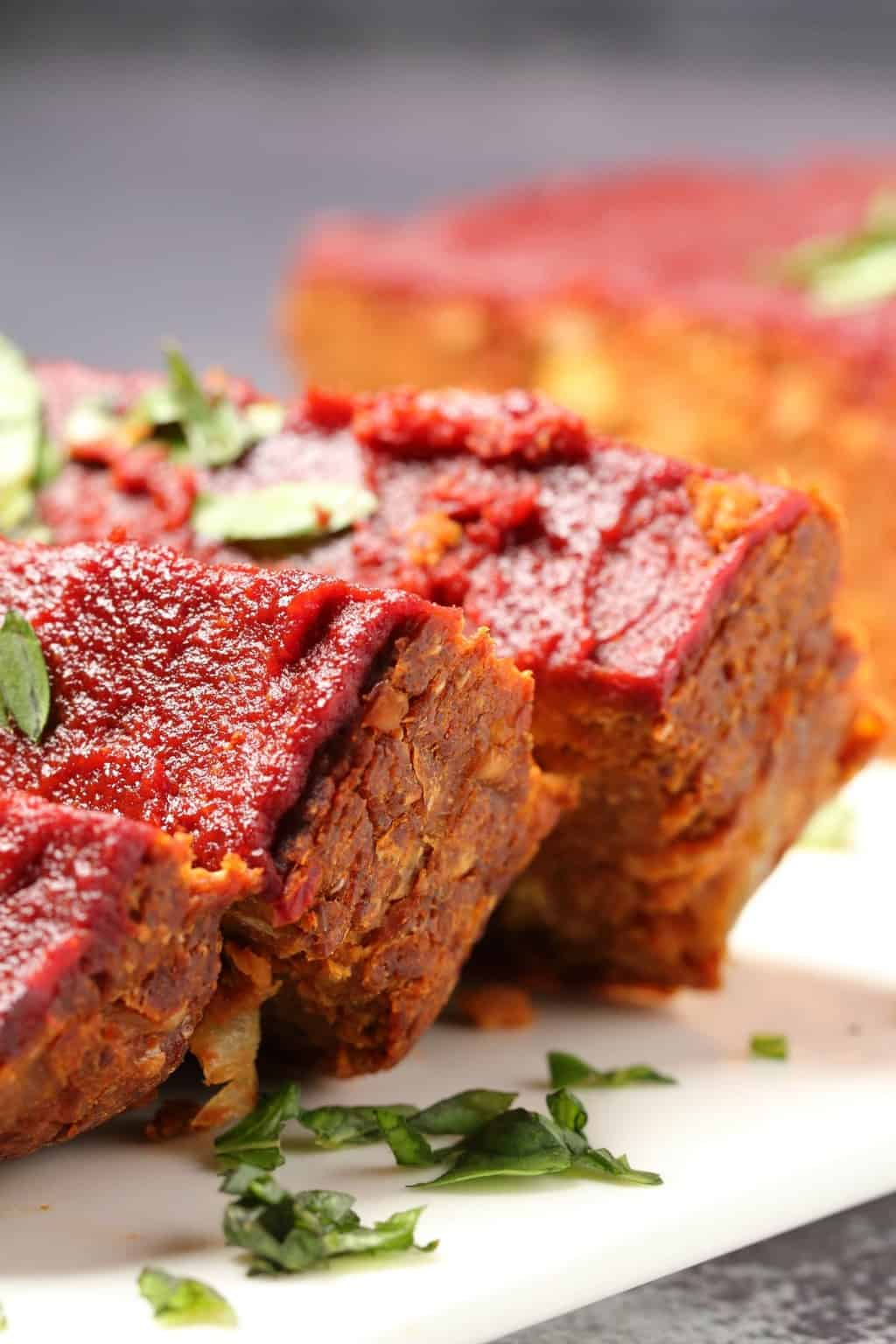 Vegan meatloaf topped with fresh basil on a white plate.