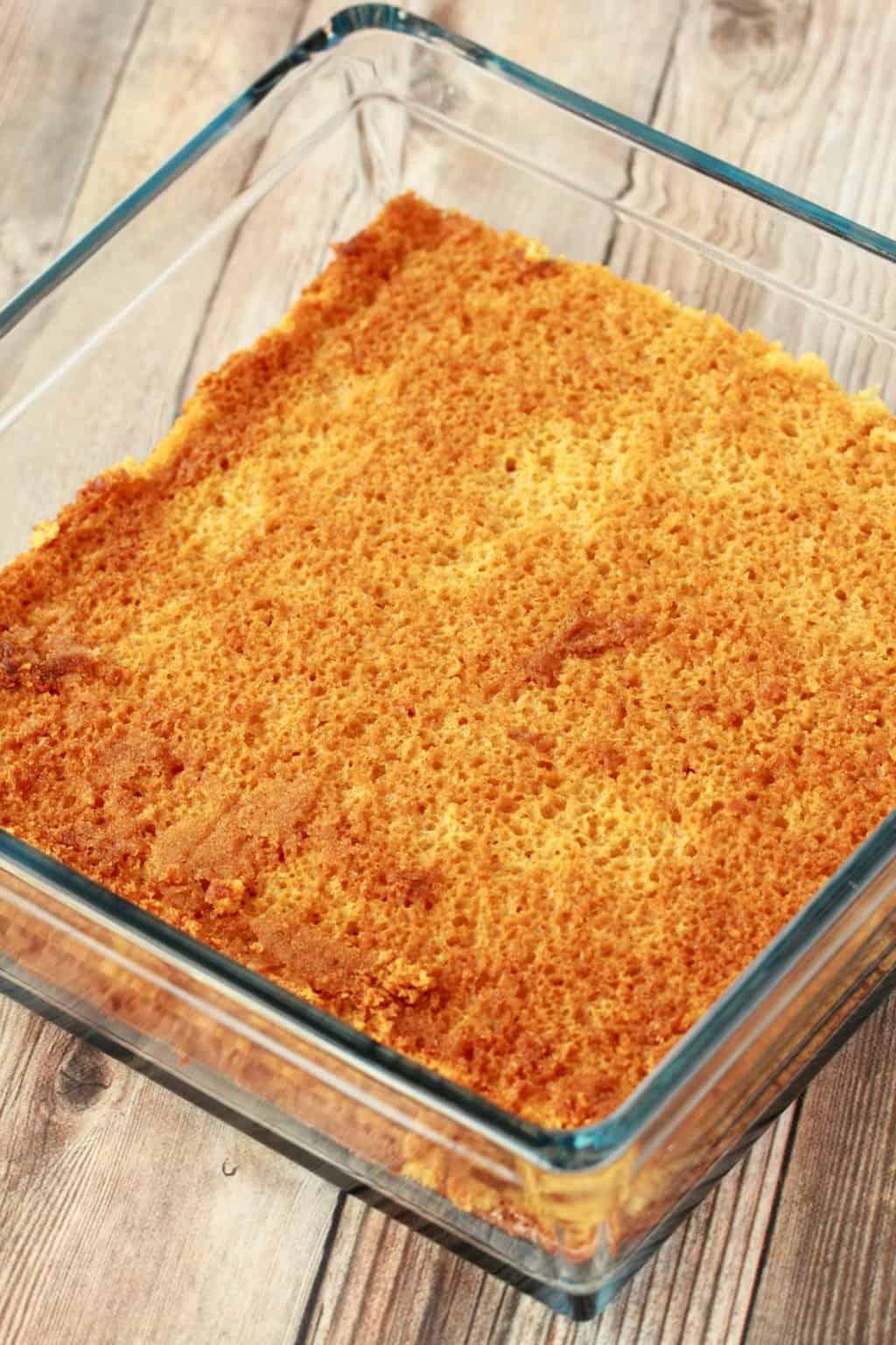 Layer of vanilla sponge cake in a glass dish.