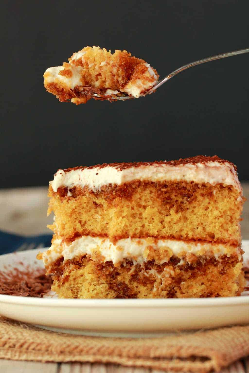 A slice of vegan tiramisu with a spoonful of tiramisu hovering over it.