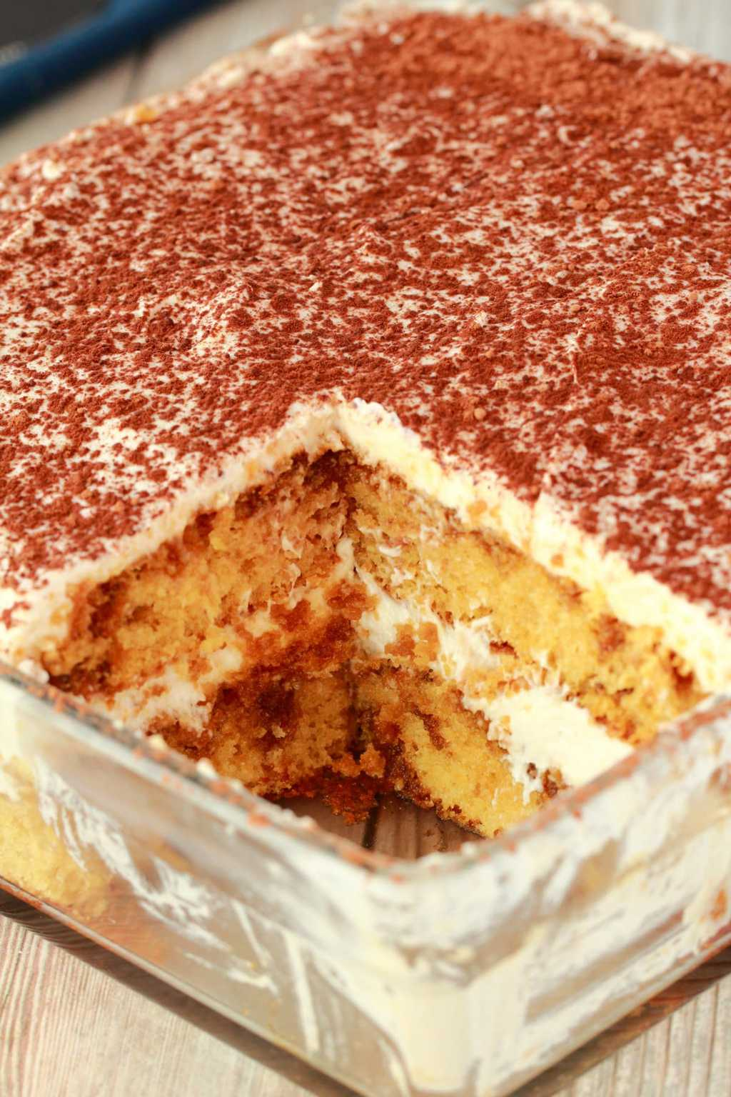 Vegan Tiramisu in a glass dish with one slice removed.