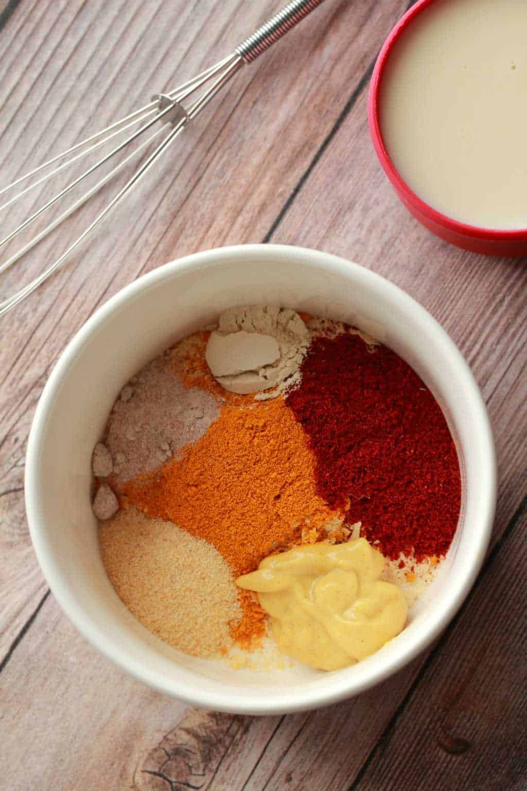 Spices in a white bowl with a mini whisk and a cup of soy milk.
