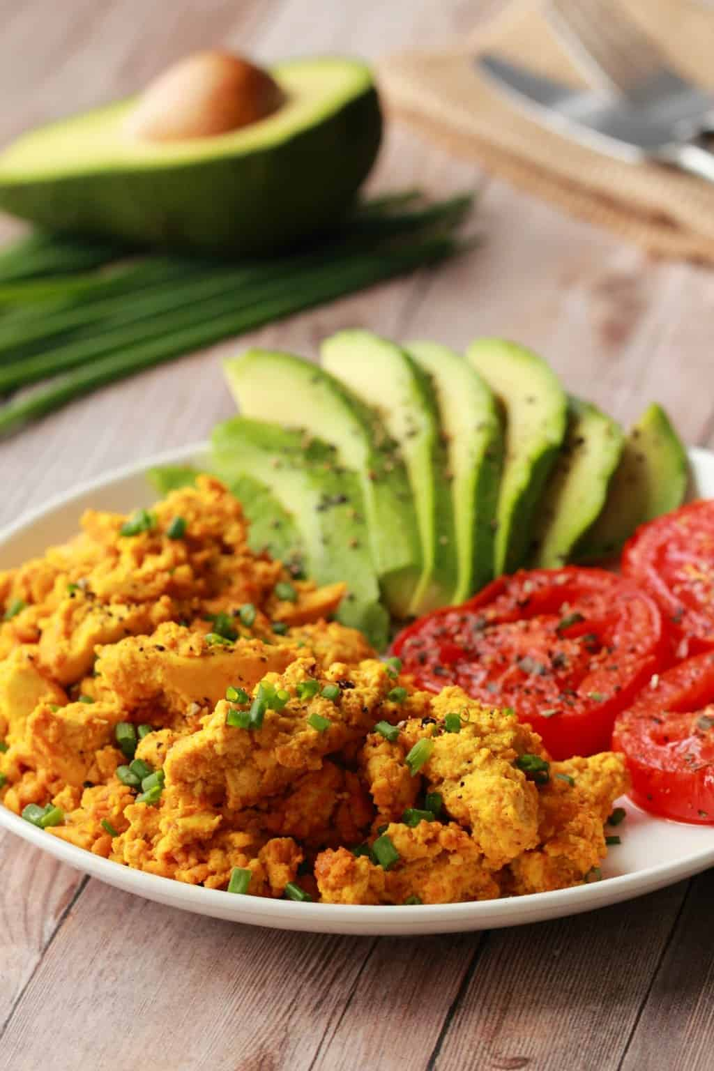 Vegan Tofu Scramble topped with chopped chives on a white plate with fried tomato and sliced avocado.
