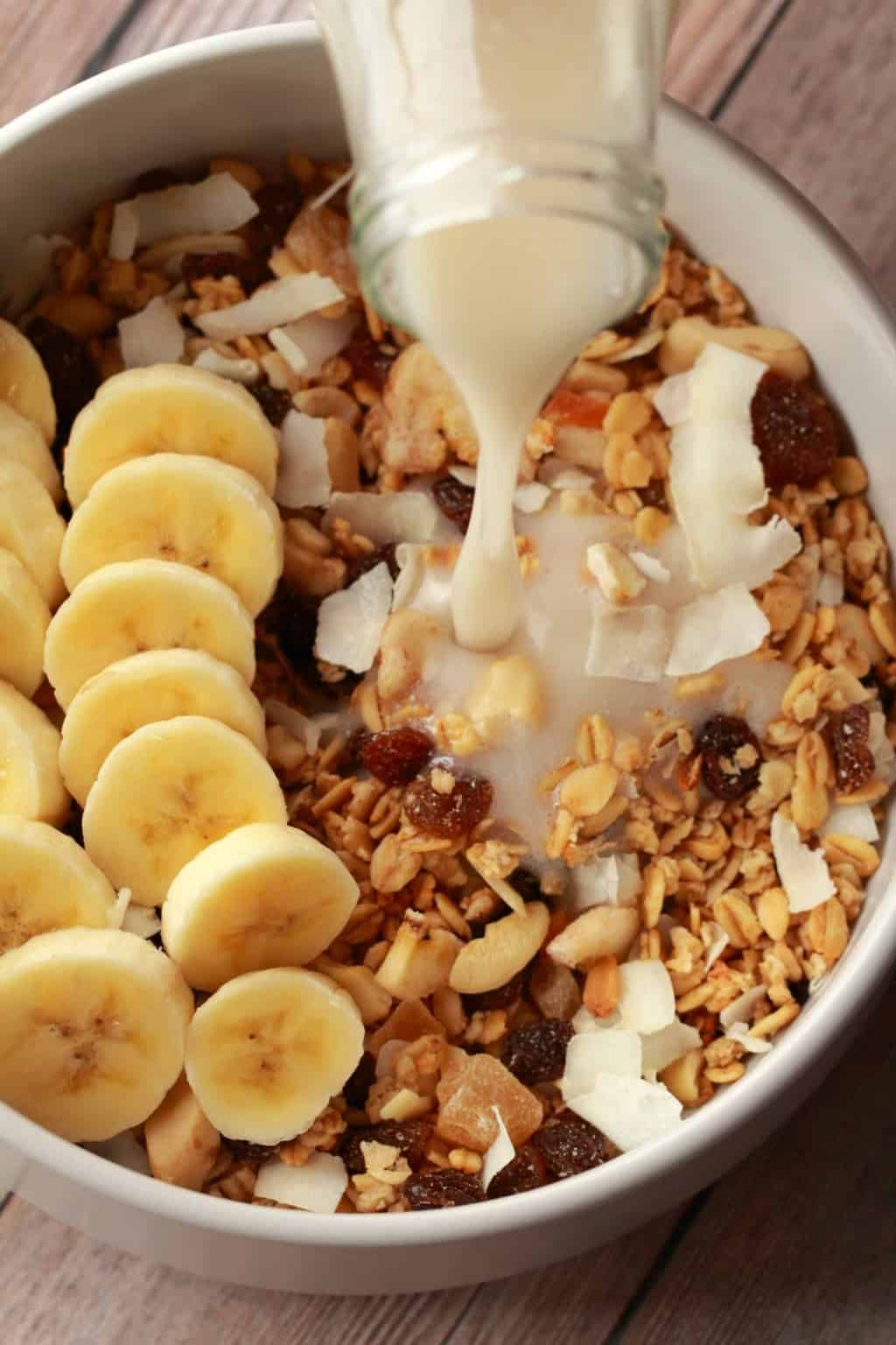 Oat milk pouring from a glass bottle into a white bowl filled with granola and sliced banana.