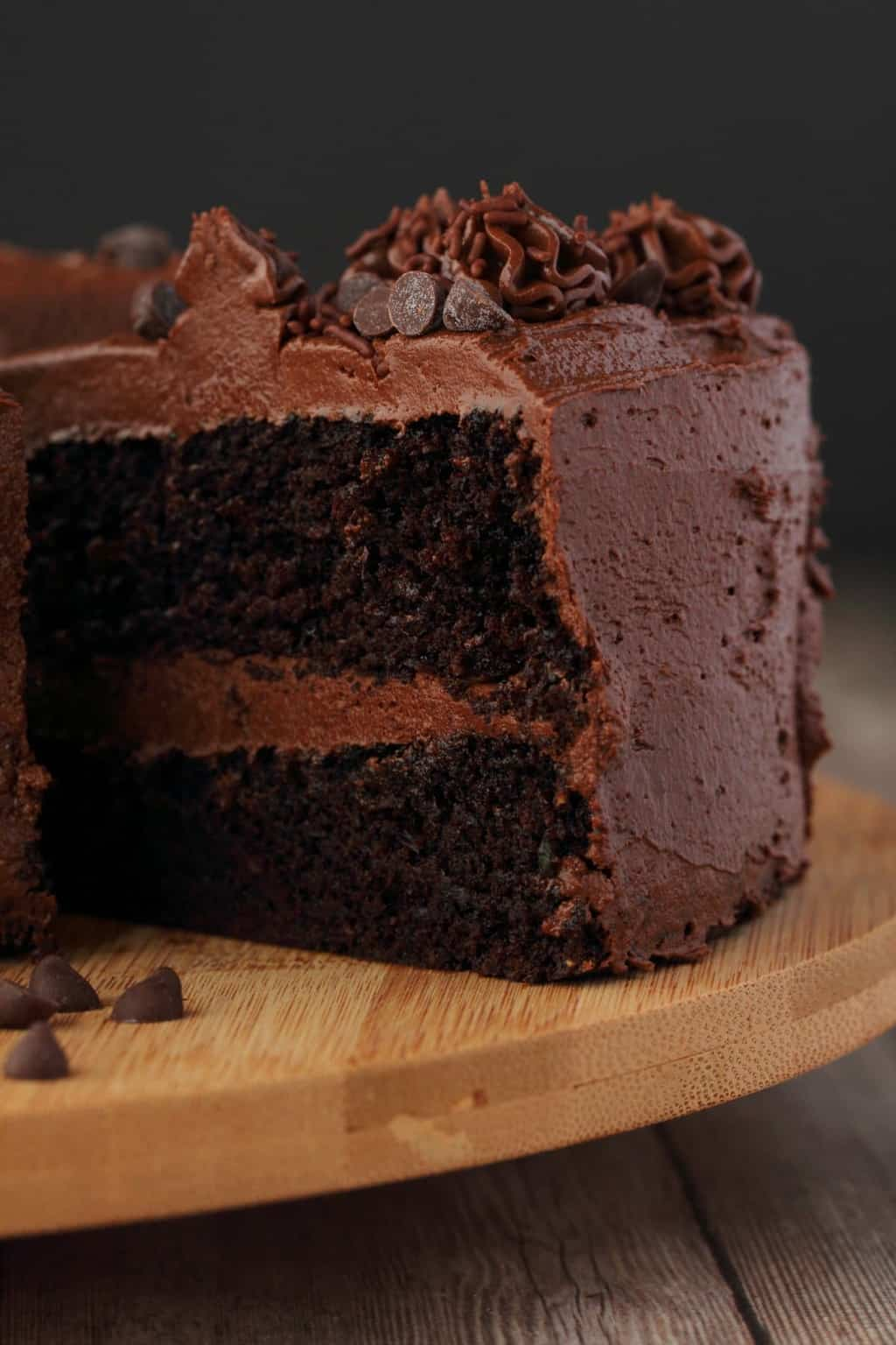 Vegan Chocolate Zucchini Cake on a wooden board with one slice cut and ready to be served.