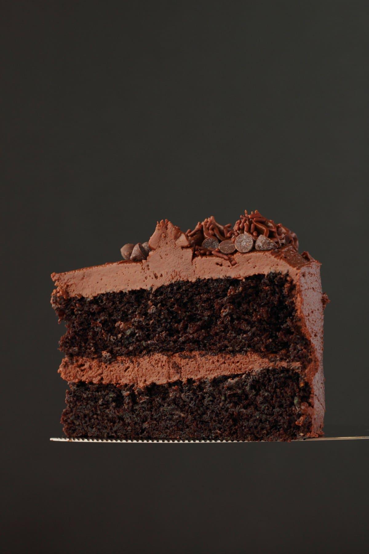 A slice of vegan chocolate zucchini cake on a cake slicer.