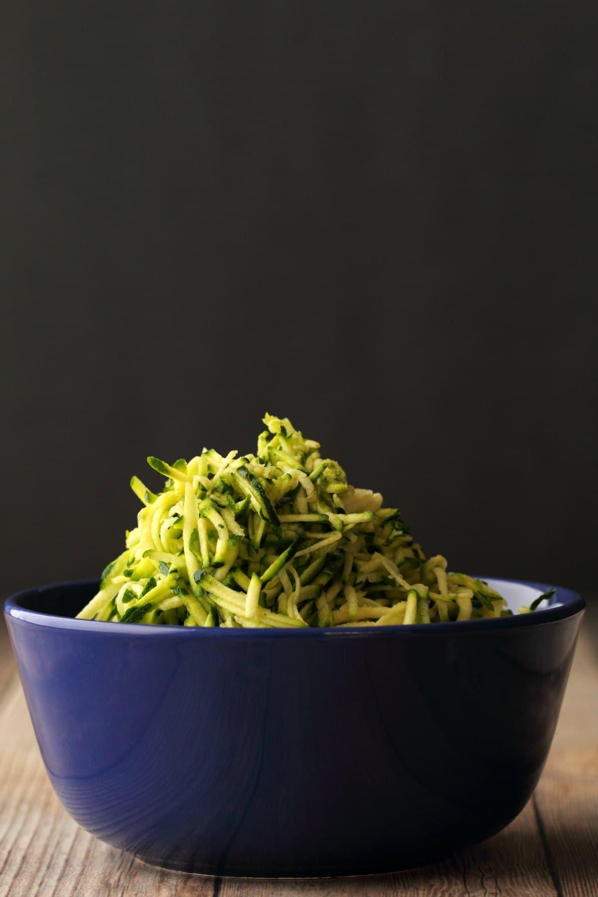 Grated zucchini in a blue bowl.