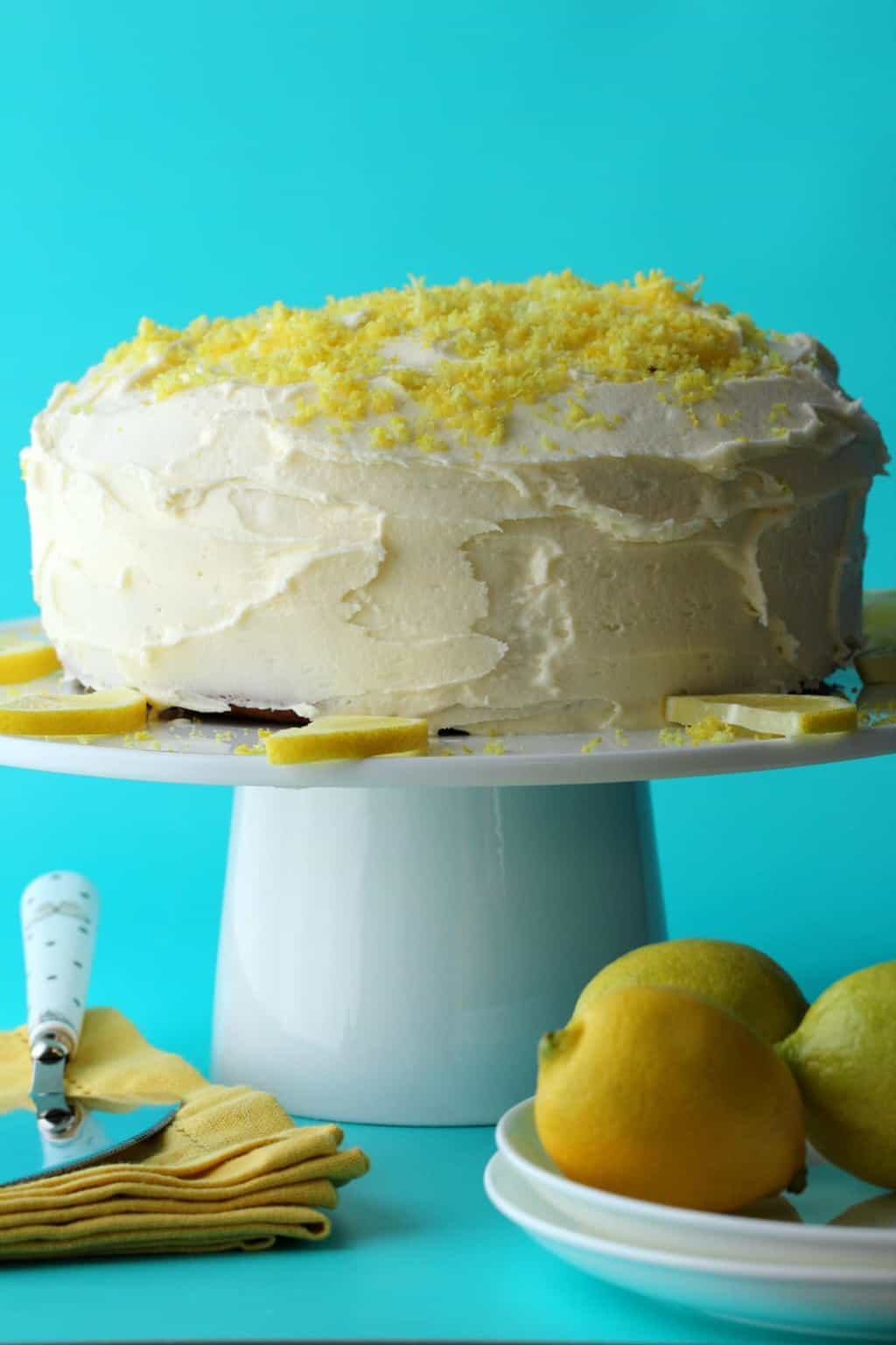 Vegan Lemon Cake on a white cake stand with lemon slices.
