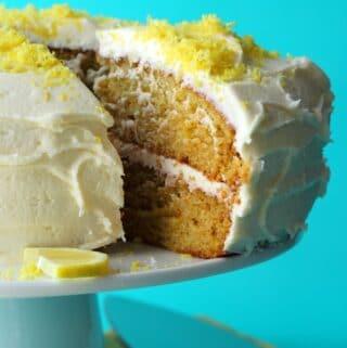 Sliced vegan lemon cake on a white cake stand.