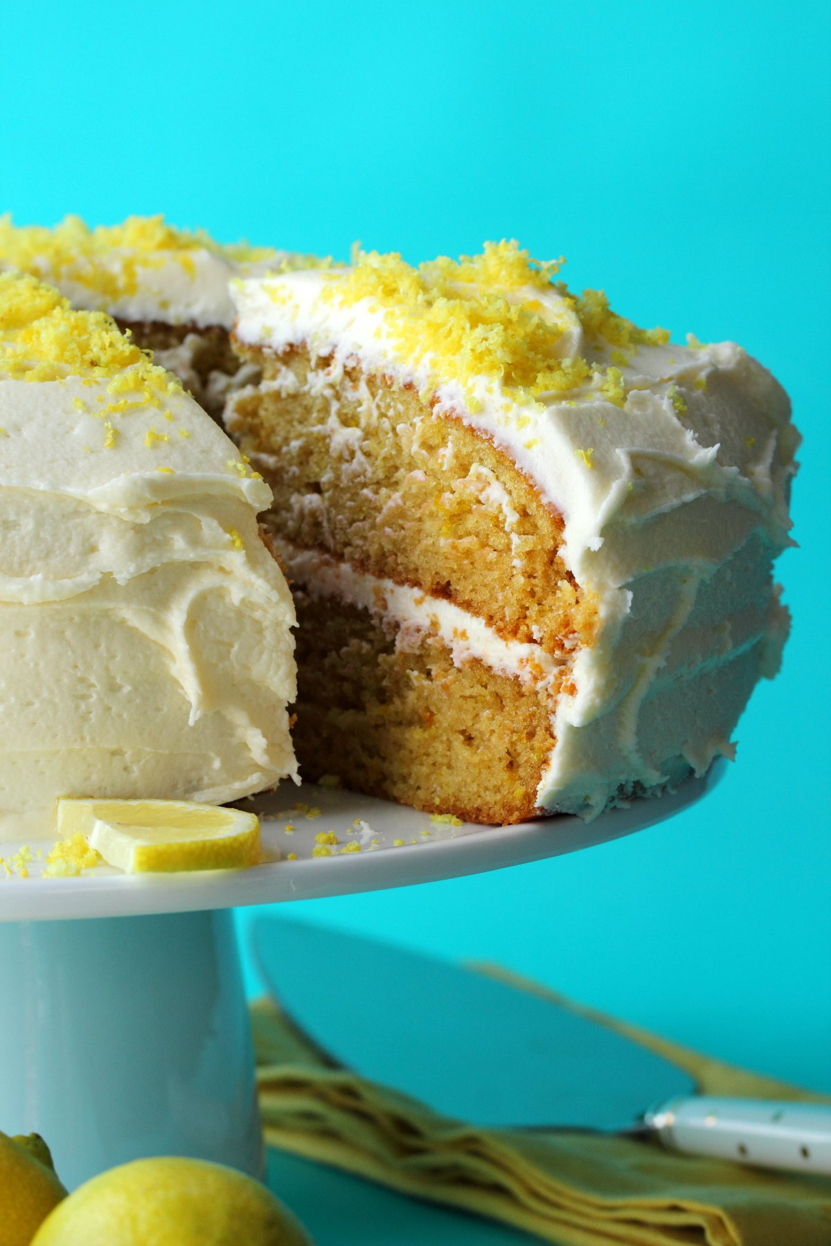 Lemon cake topped with lemon zest on a white cake stand.
