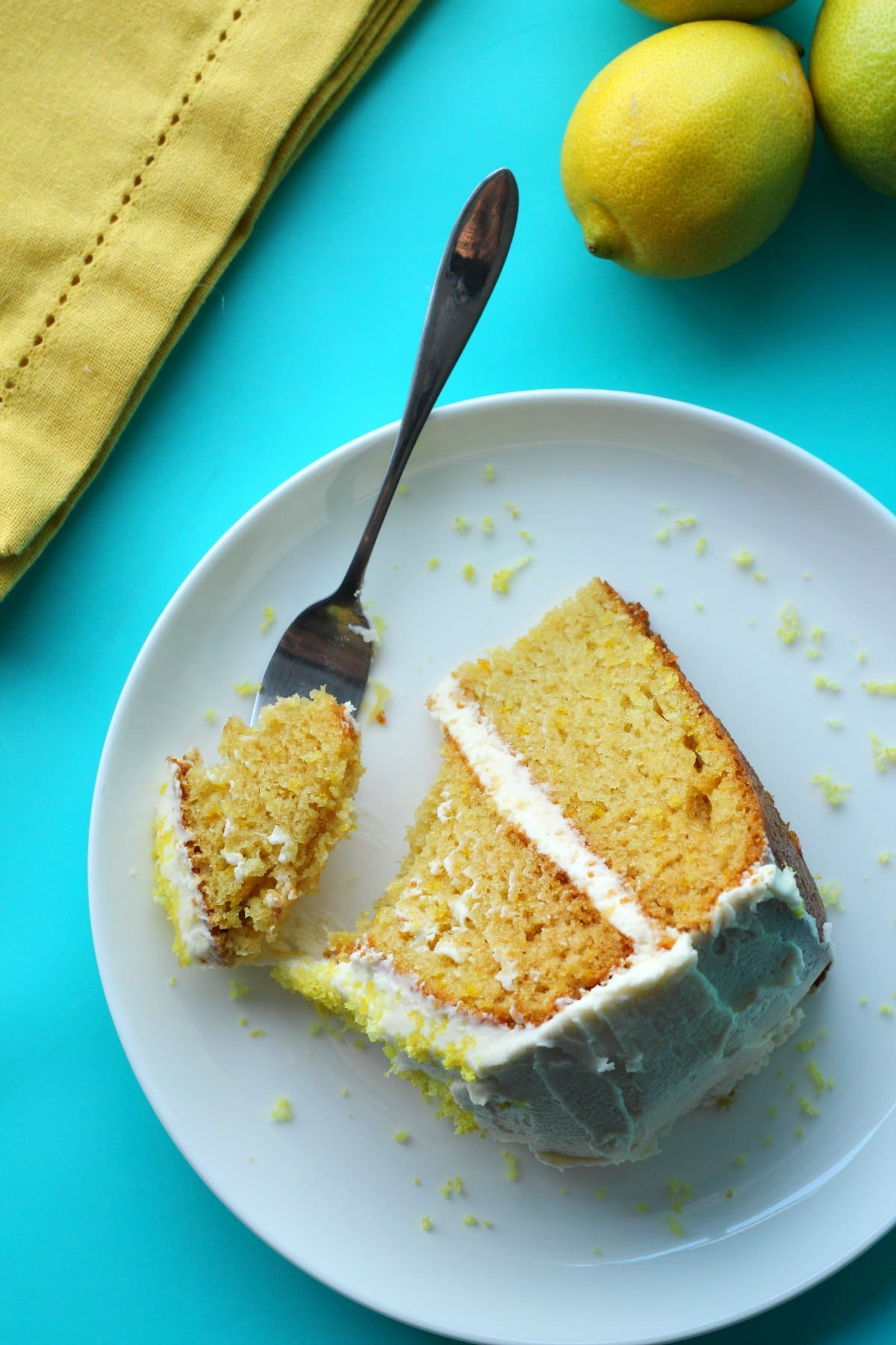 A slice of lemon cake on a white plate with a cake fork.
