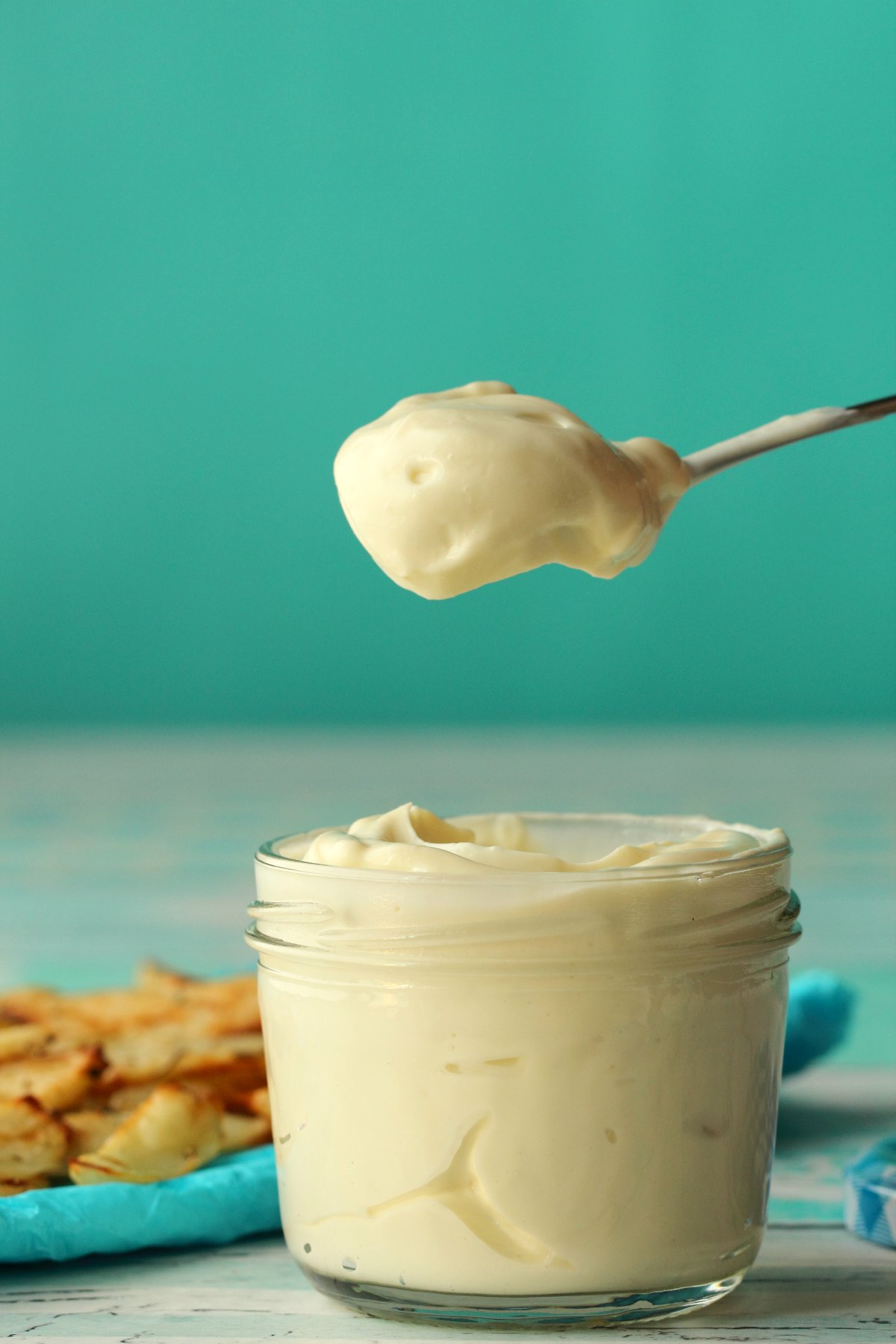 A spoonful of vegan mayo above a glass jar of mayo.