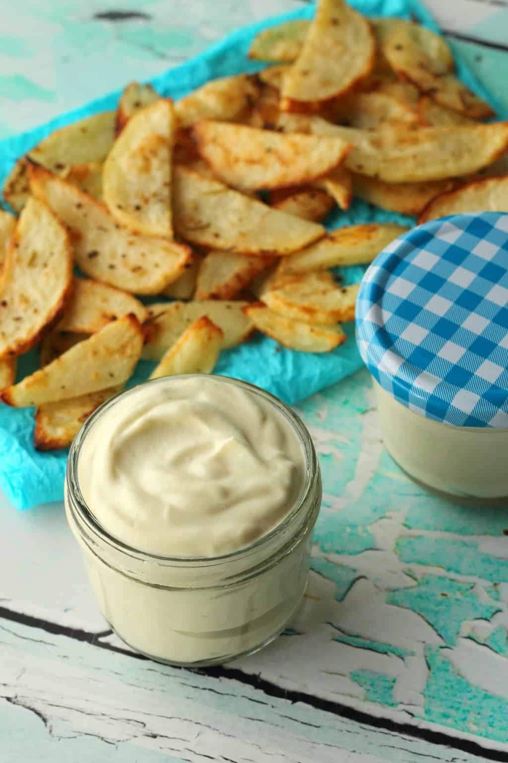 Vegan Mayo in a glass jar with baked potato chips in the background.