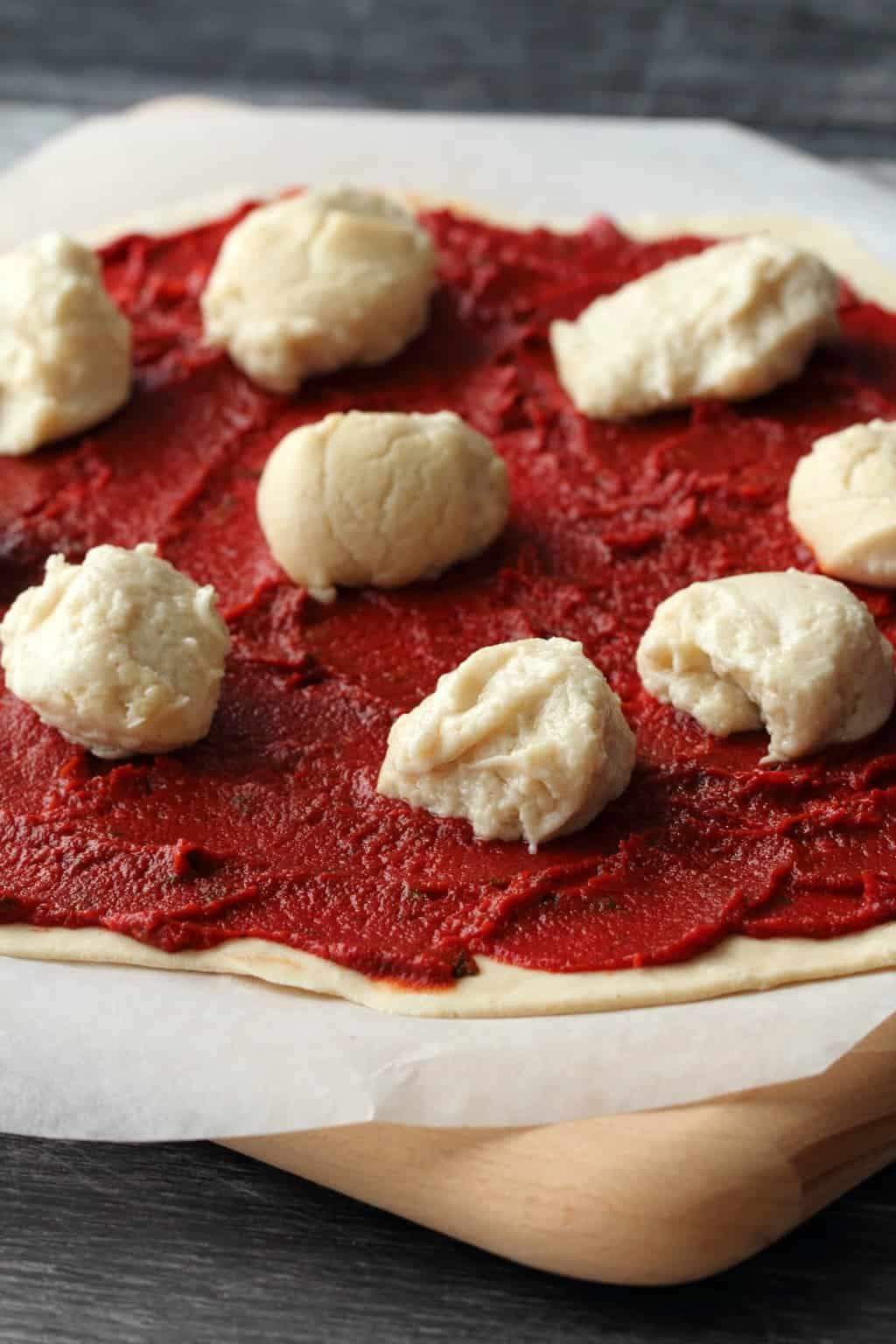 Vegan Mozzarella balls on top of a pizza ready to go into the oven.