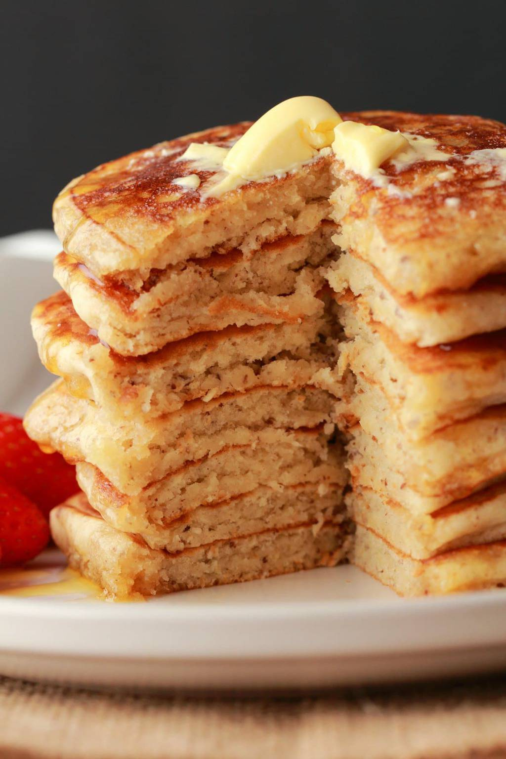 Vegan pancakes in a stack with a triangle shape cut out of the stack.