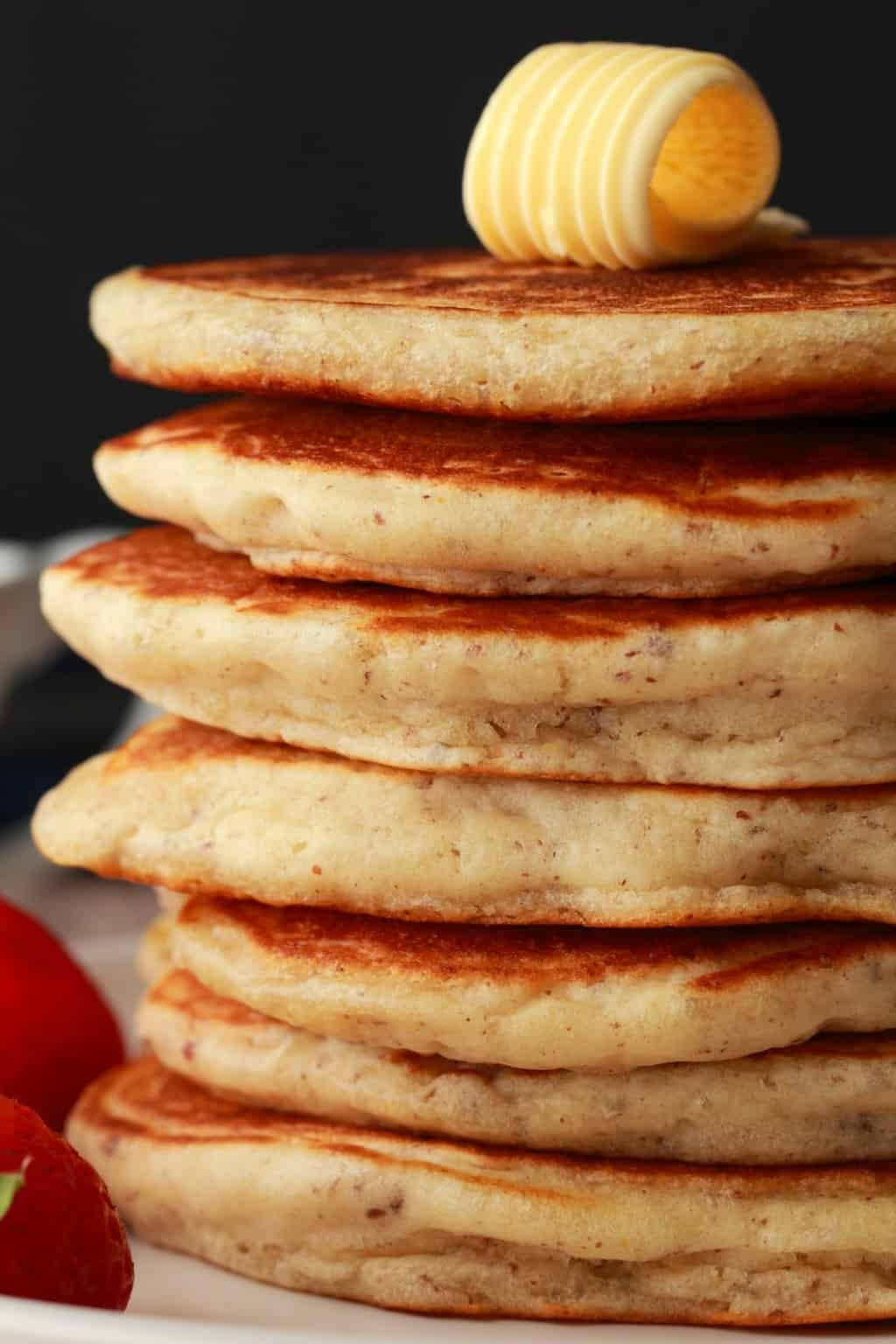 A stack of vegan pancakes with a pat of butter on top.