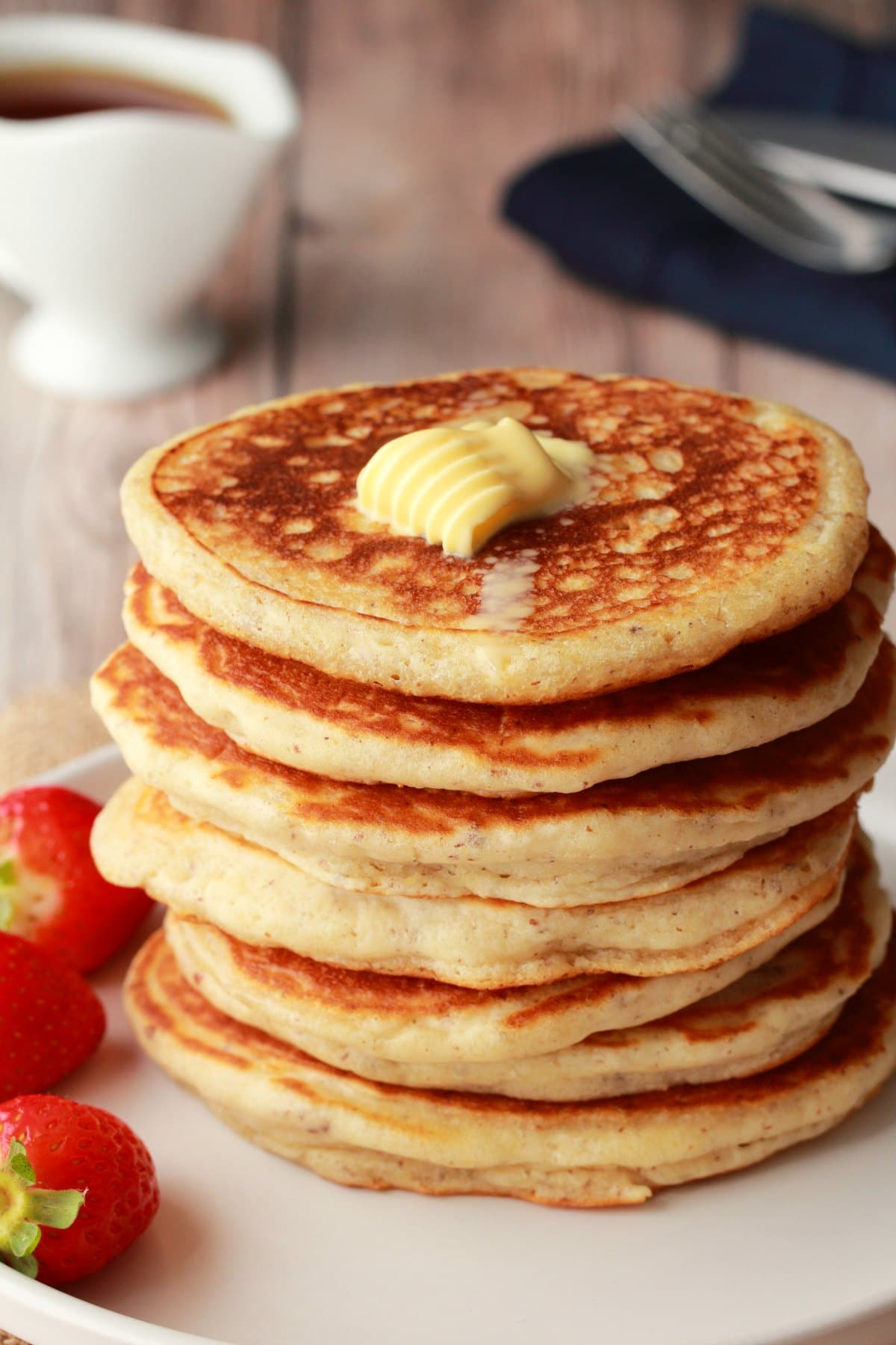 A stack of vegan pancakes with a pat of butter on top, some strawberries and a jug of syrup.