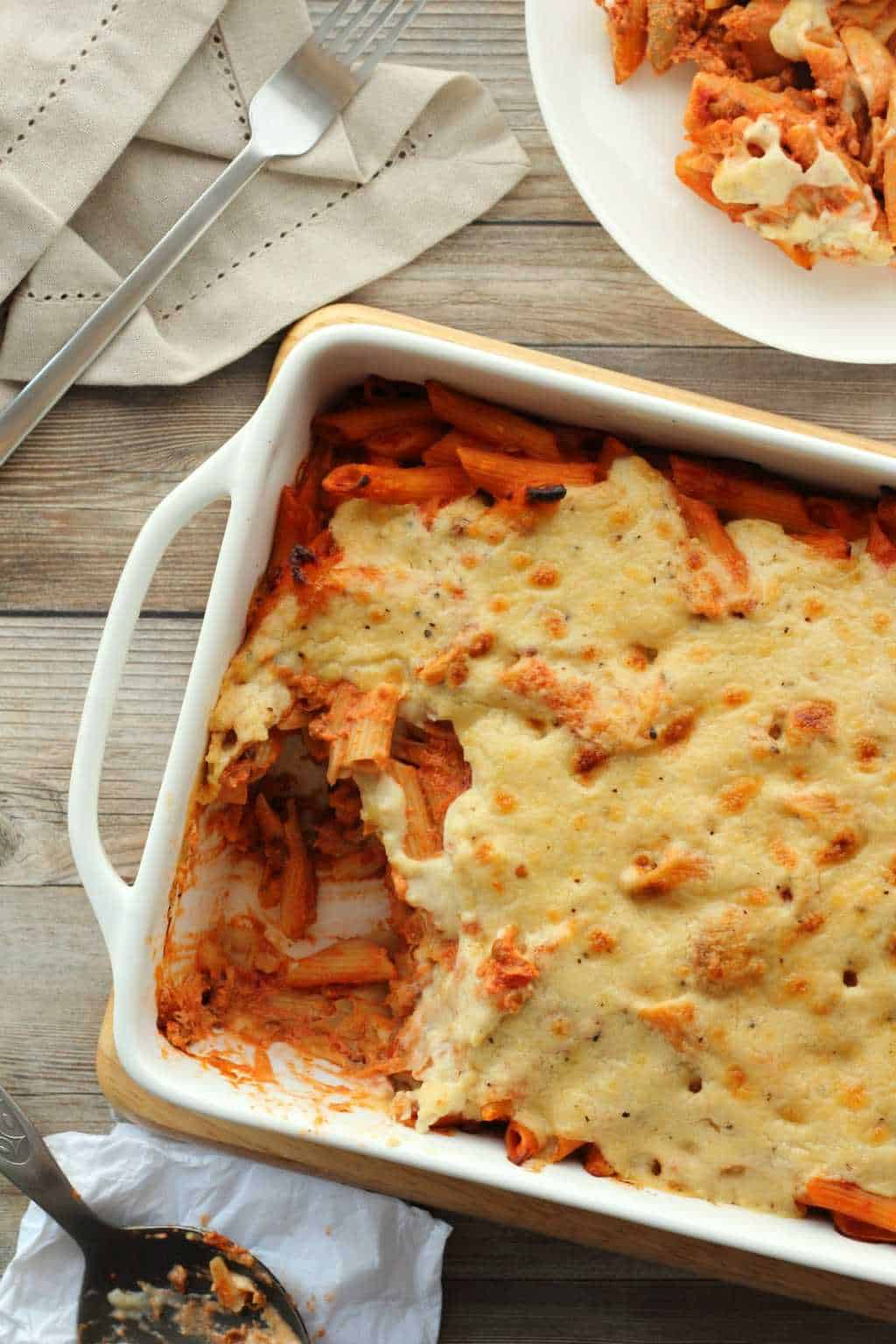 Vegan Pasta Bake in a white oven dish with a side plate.
