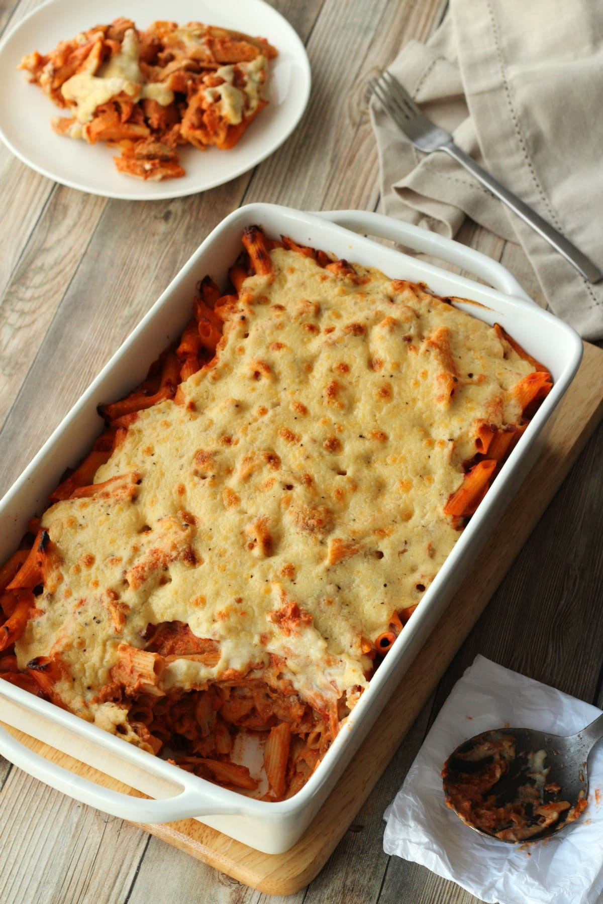 Vegan Pasta Bake in a white oven dish with a serving dished up on a white side plate.