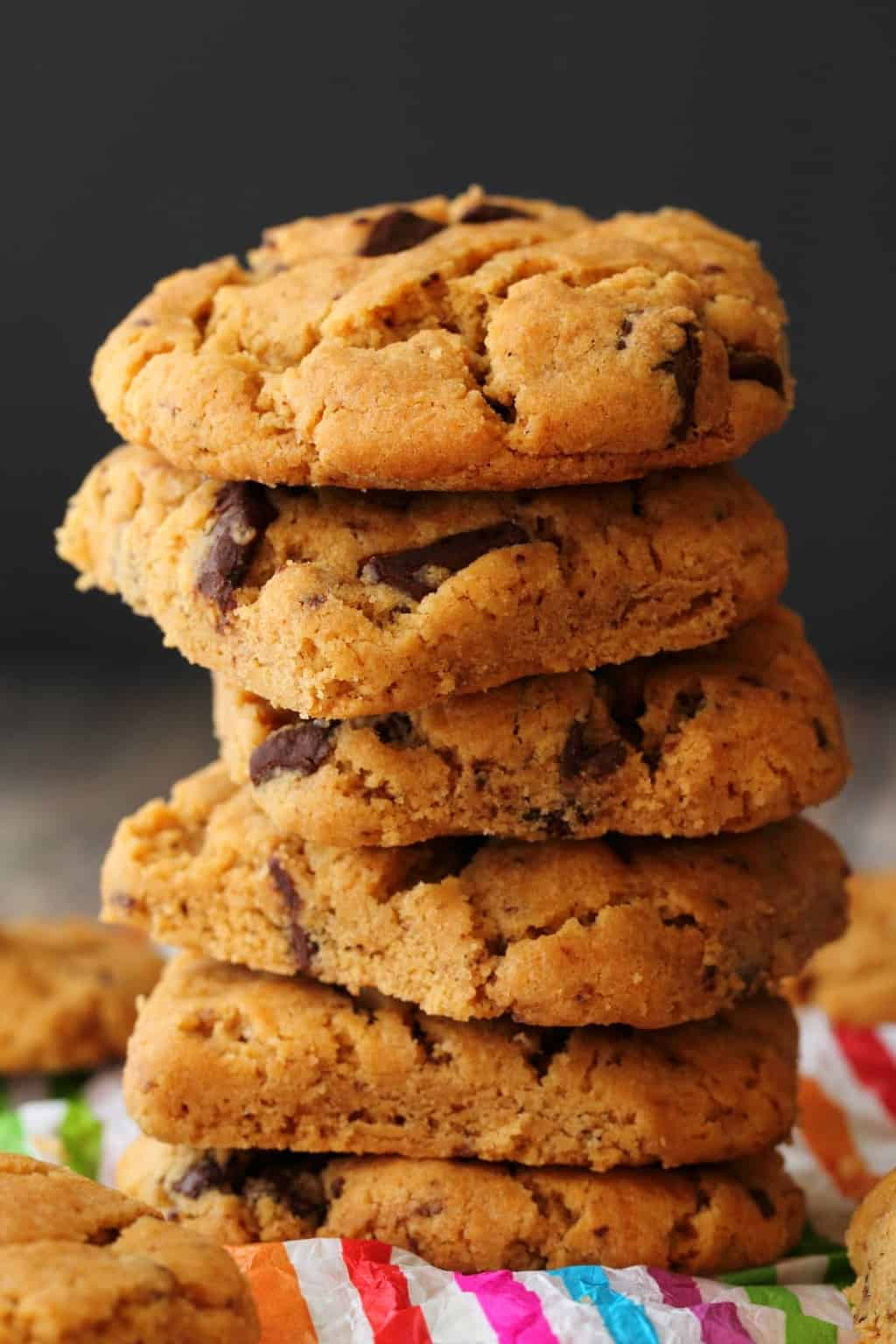 Vegan Peanut Butter Chocolate Chip Cookies in a stack against a dark background.