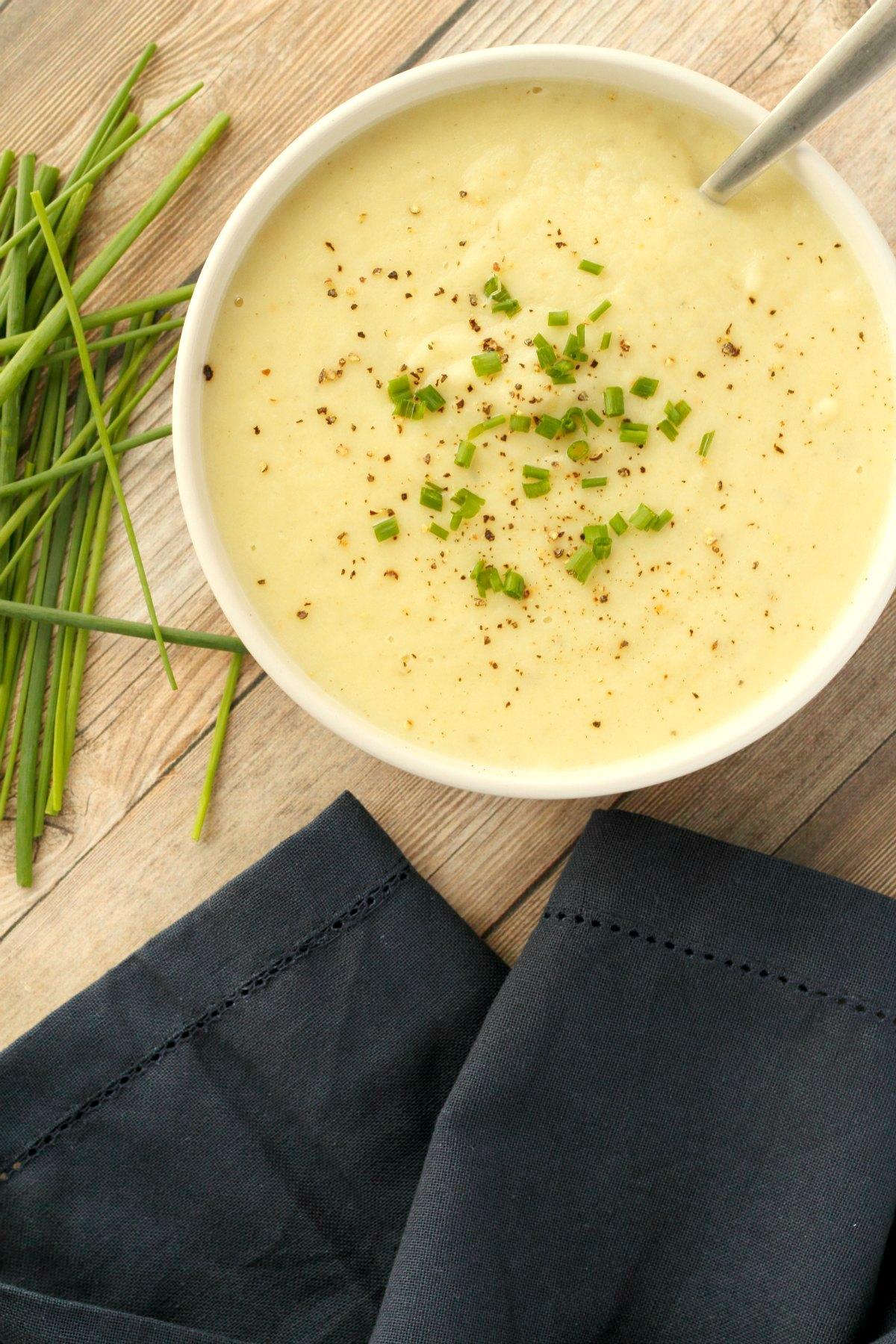 Vegan potato leek soup in a white bowl with a spoon.