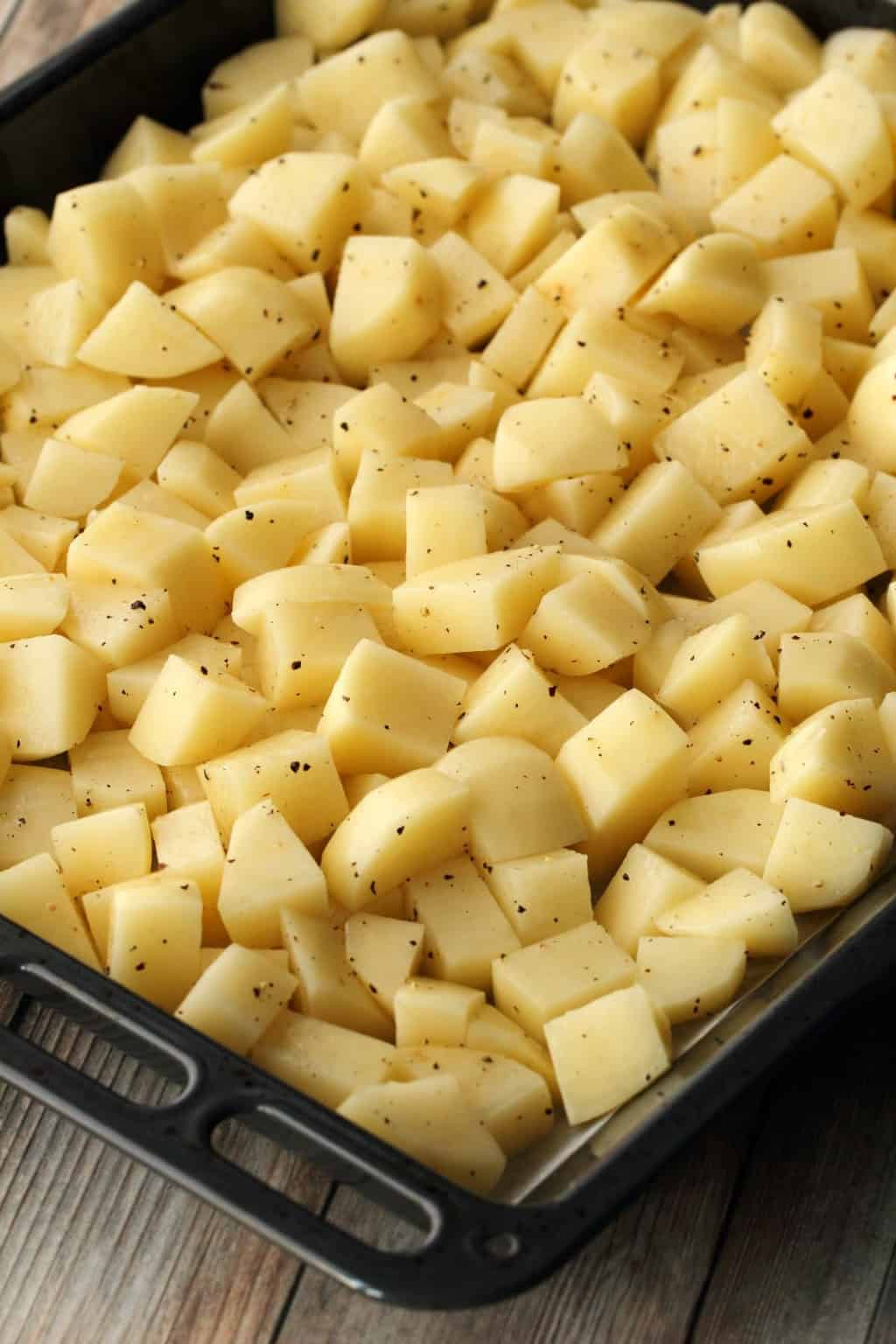Chopped potatoes on a baking tray ready to go into the oven.