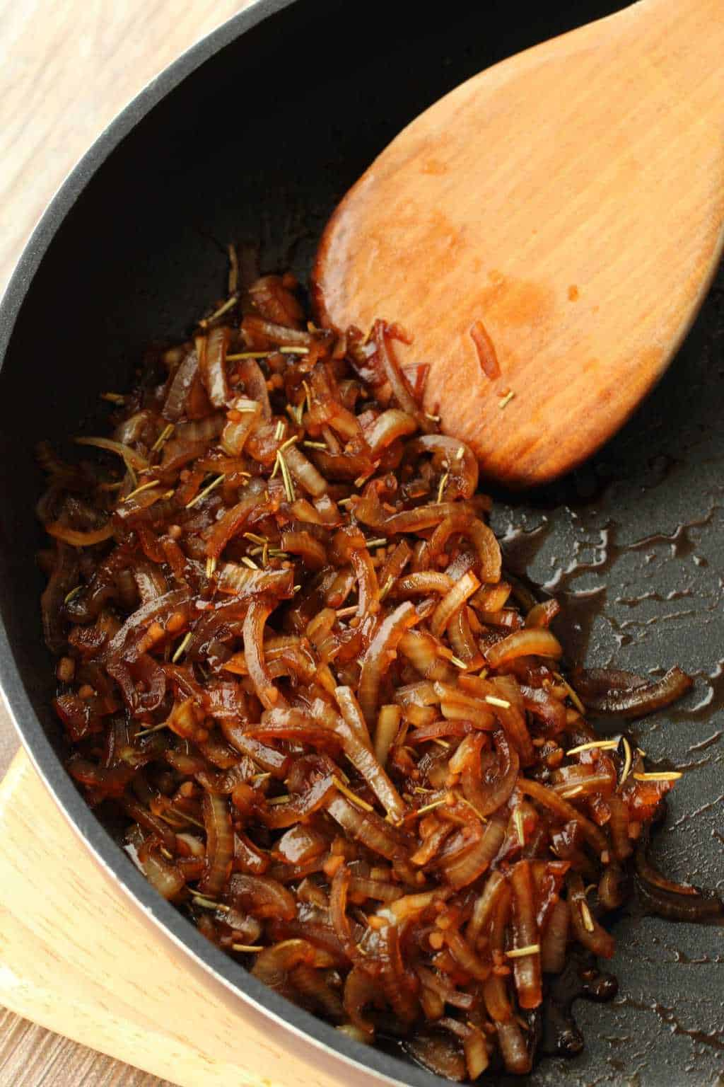 Fried onions and garlic in soy sauce and spices in a frying pan with a wooden spoon.
