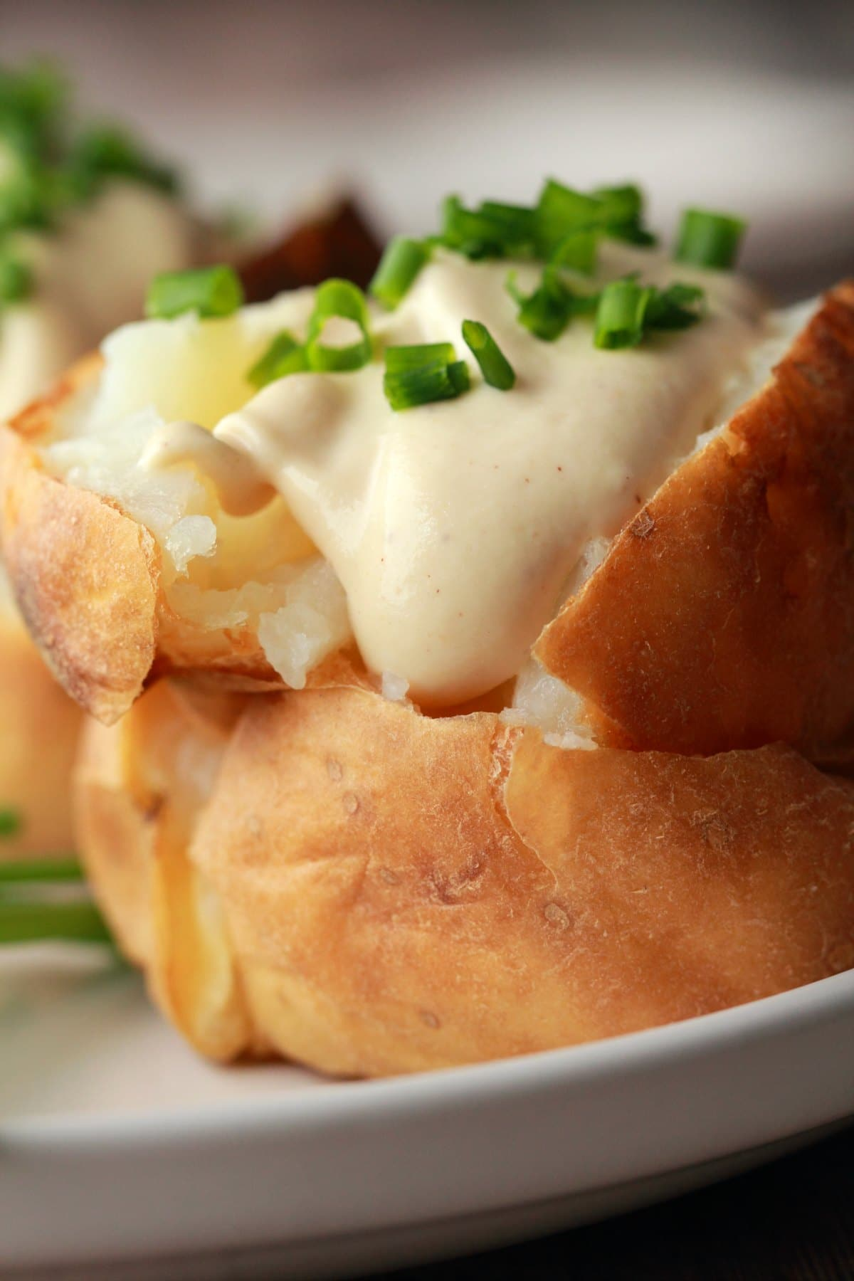 Baked potato topped with sour cream and chives.