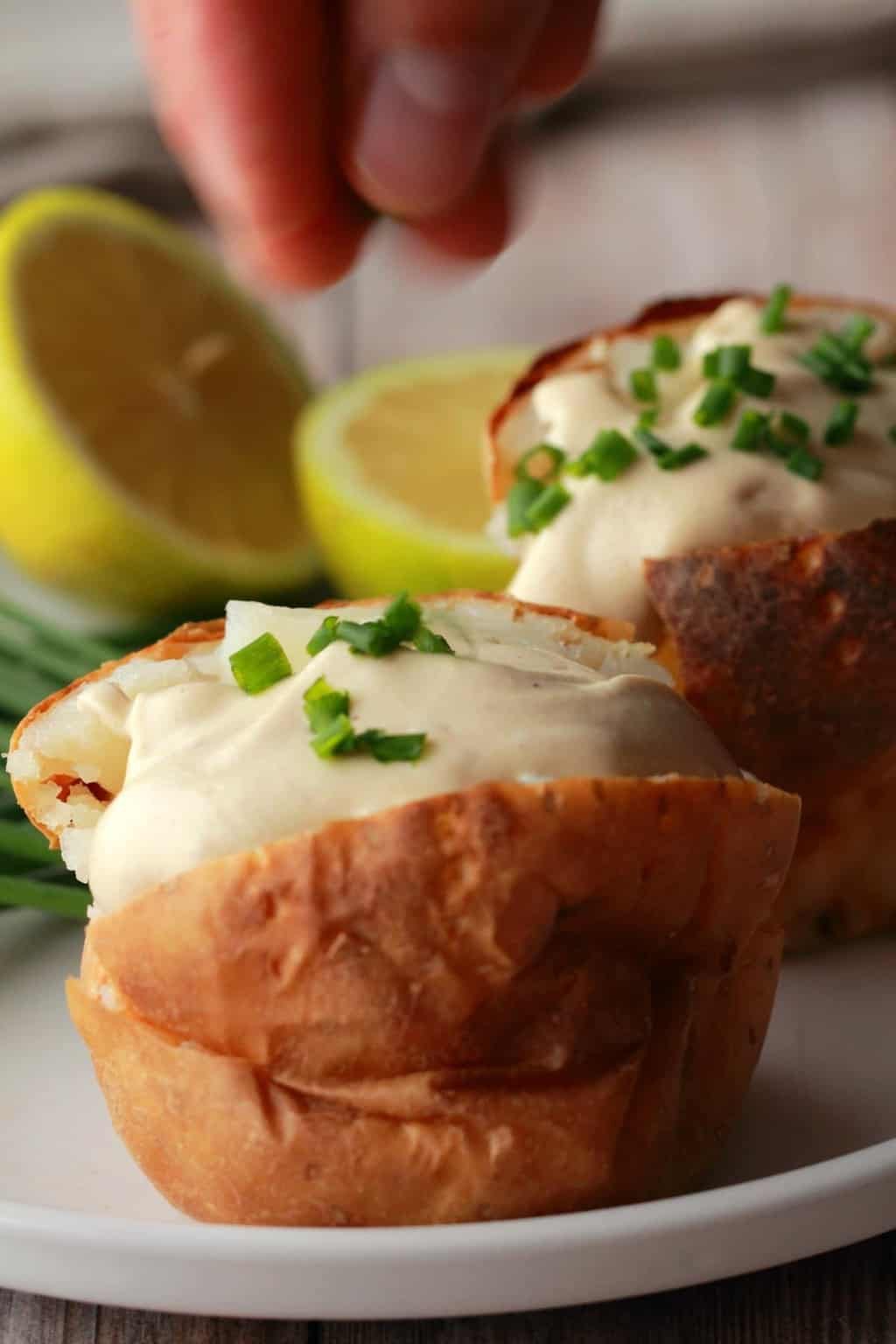 Vegan Sour Cream and chopped chives on top of a baked potato.