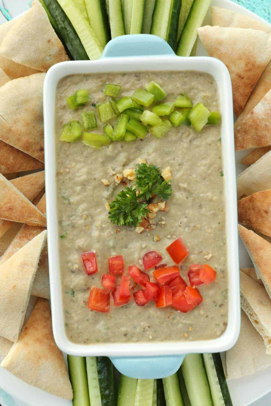 Eggplant Dip in a blue and white serving dish surrounded by pita breads and cucumber slices.