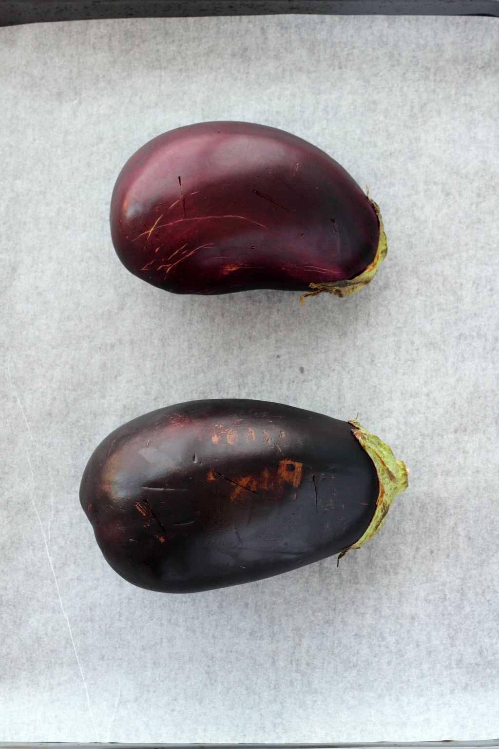 Two raw eggplants on a parchment lined baking tray, about to go into the oven.