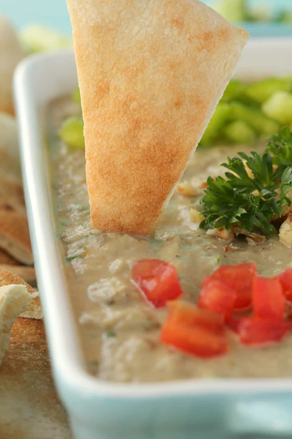 A pita bread dipping into eggplant dip in a blue and white serving dish.