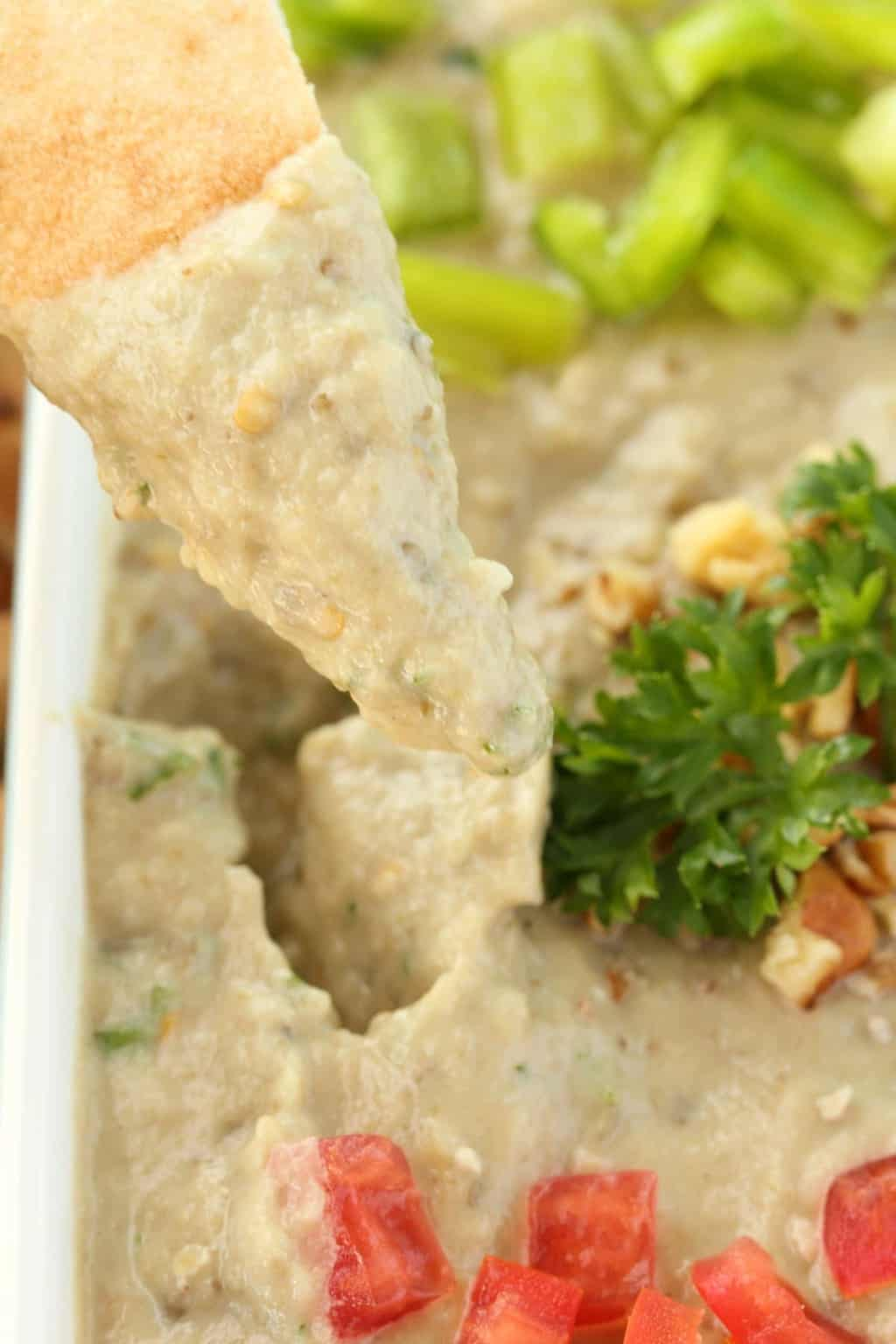 A pita bread dipping into eggplant dip in a white serving dish.