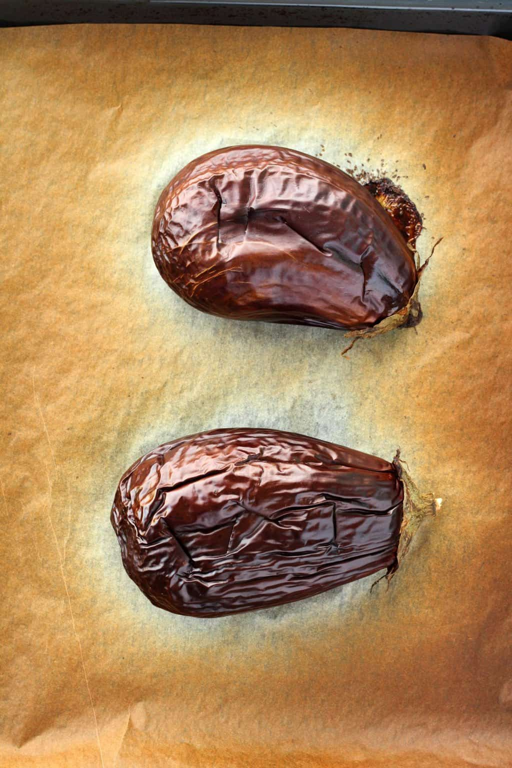 Two cooked eggplants on a parchment lined baking tray, straight out of the oven.