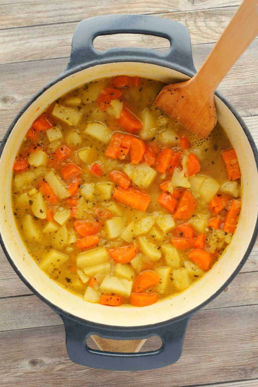 Vegetables and stock in a cast iron pot with a wooden spoon making vegan broccoli cheese soup.