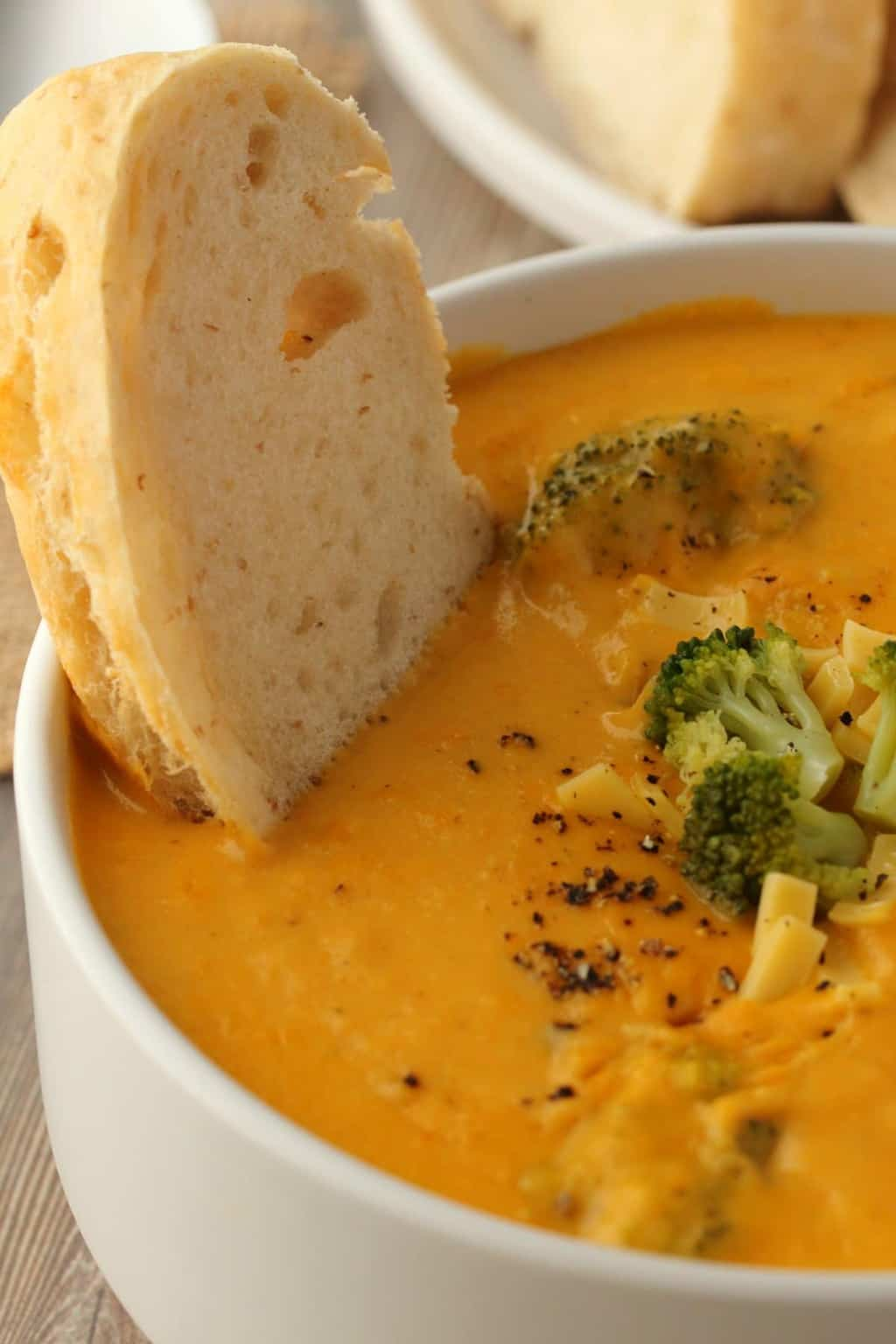 A piece of bread dipping into a bowl of vegan broccoli cheese soup.