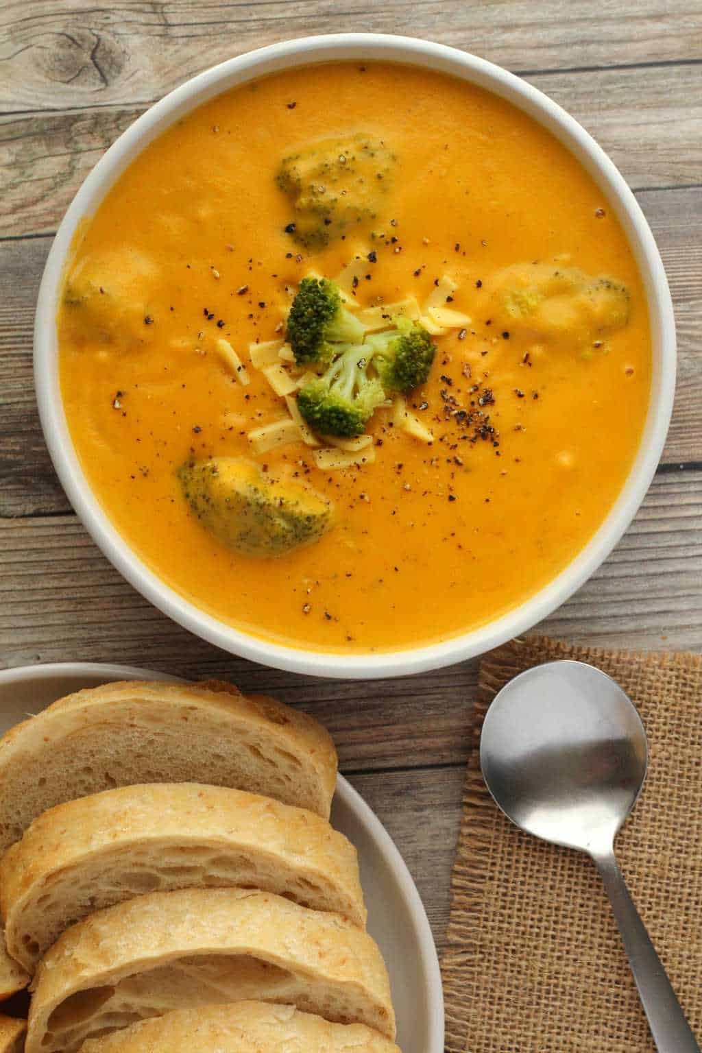Vegan Broccoli Cheese Soup topped with grated vegan cheese and black pepper in a white bowl.