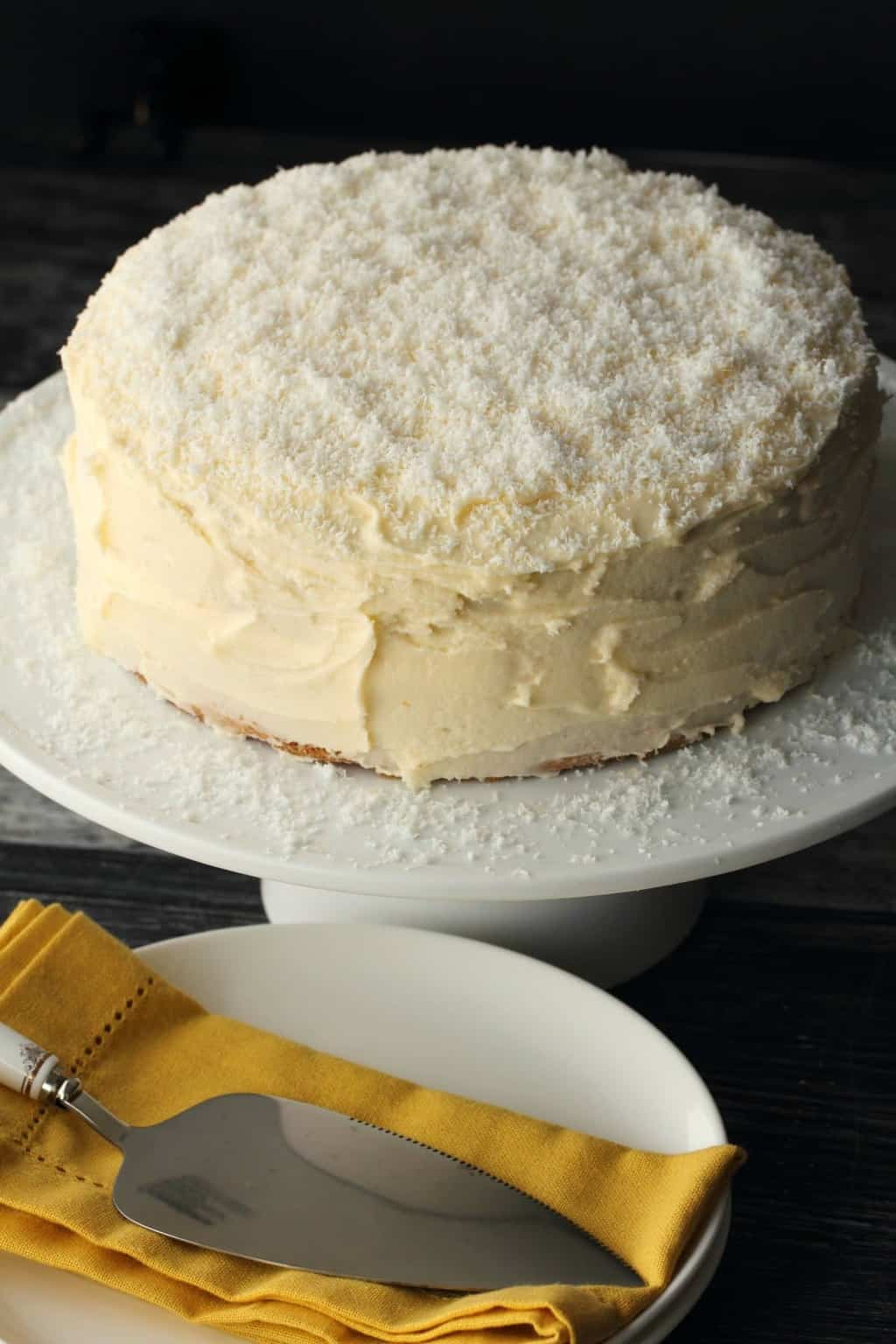 Vegan Coconut Cake on a white cake stand.