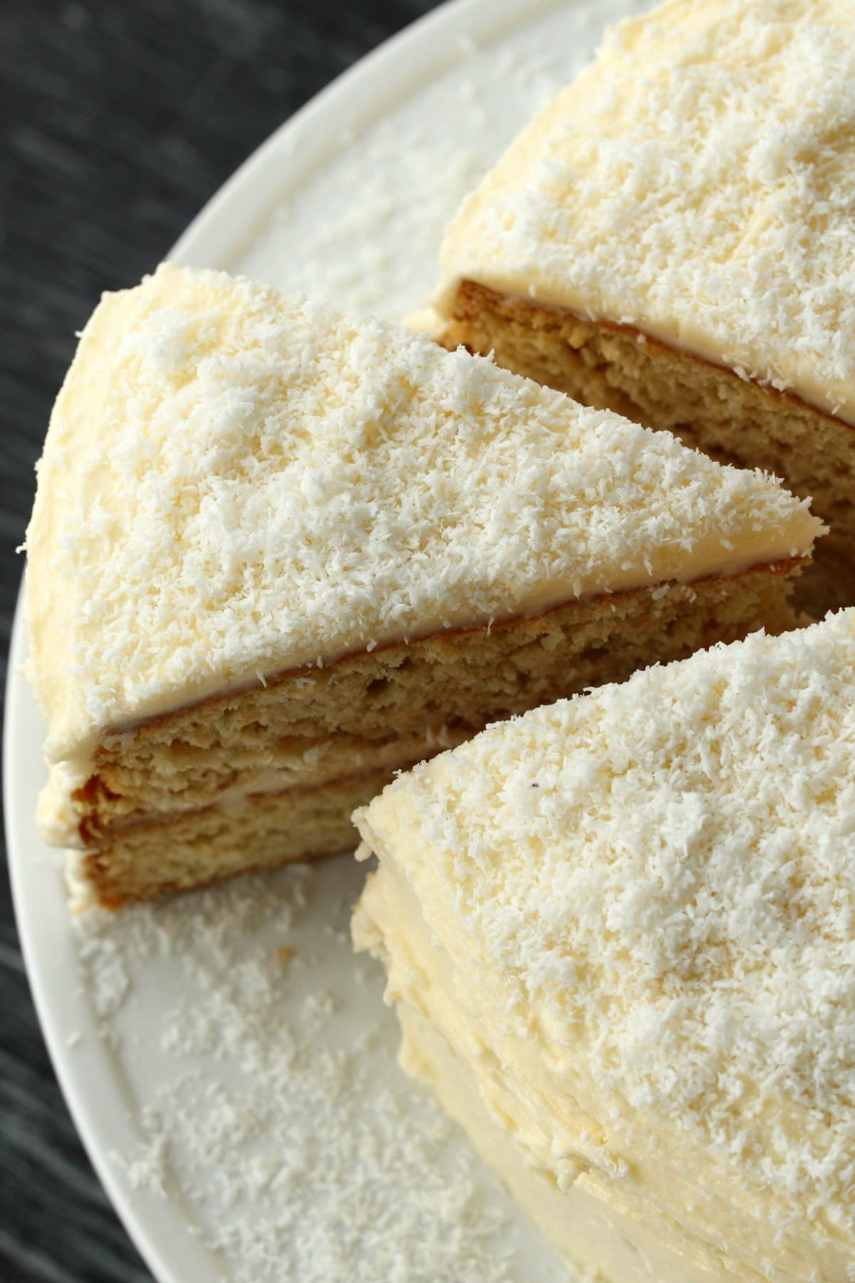 Vegan Coconut Cake on a white cake stand with one slice cut and ready to be served.