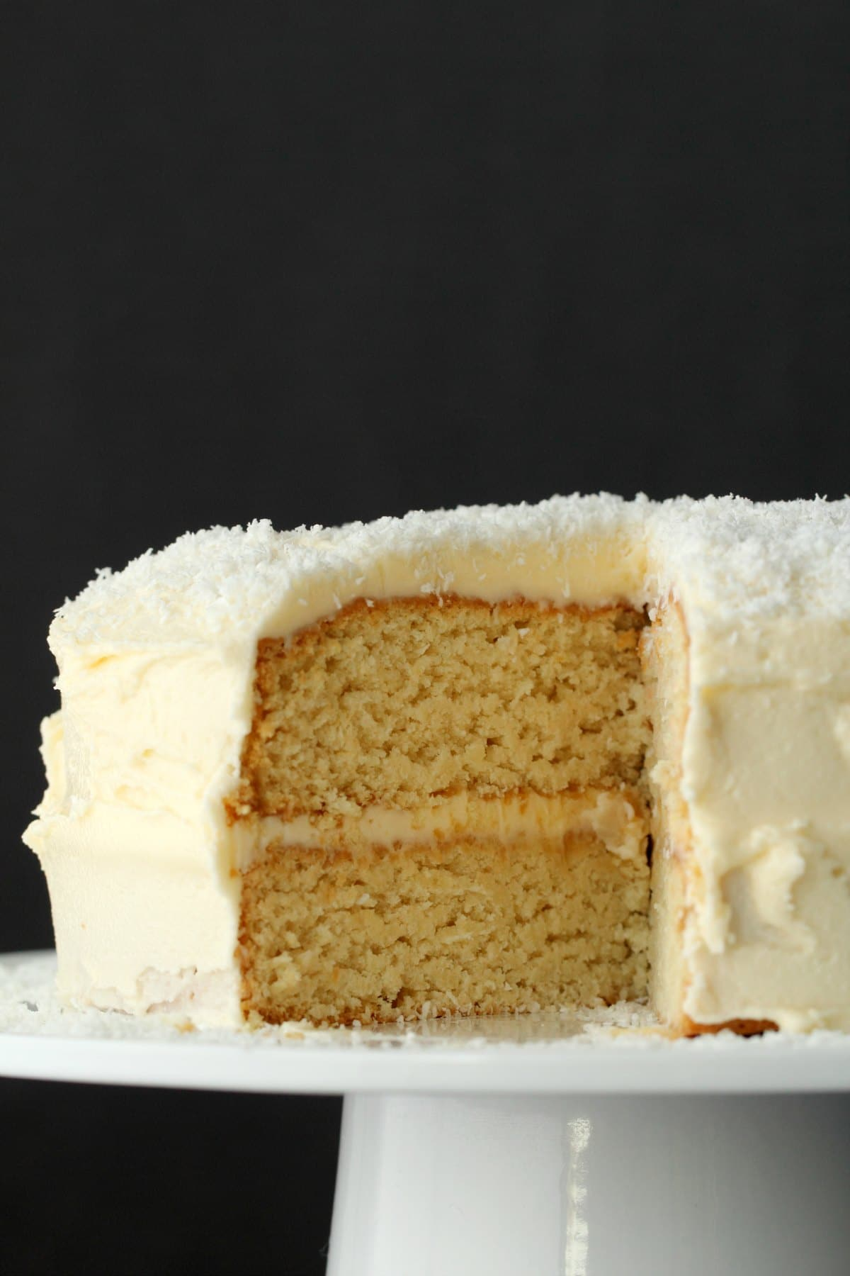 Vegan Coconut Cake on a white cake stand with one slice missing showing the inside of the cake.