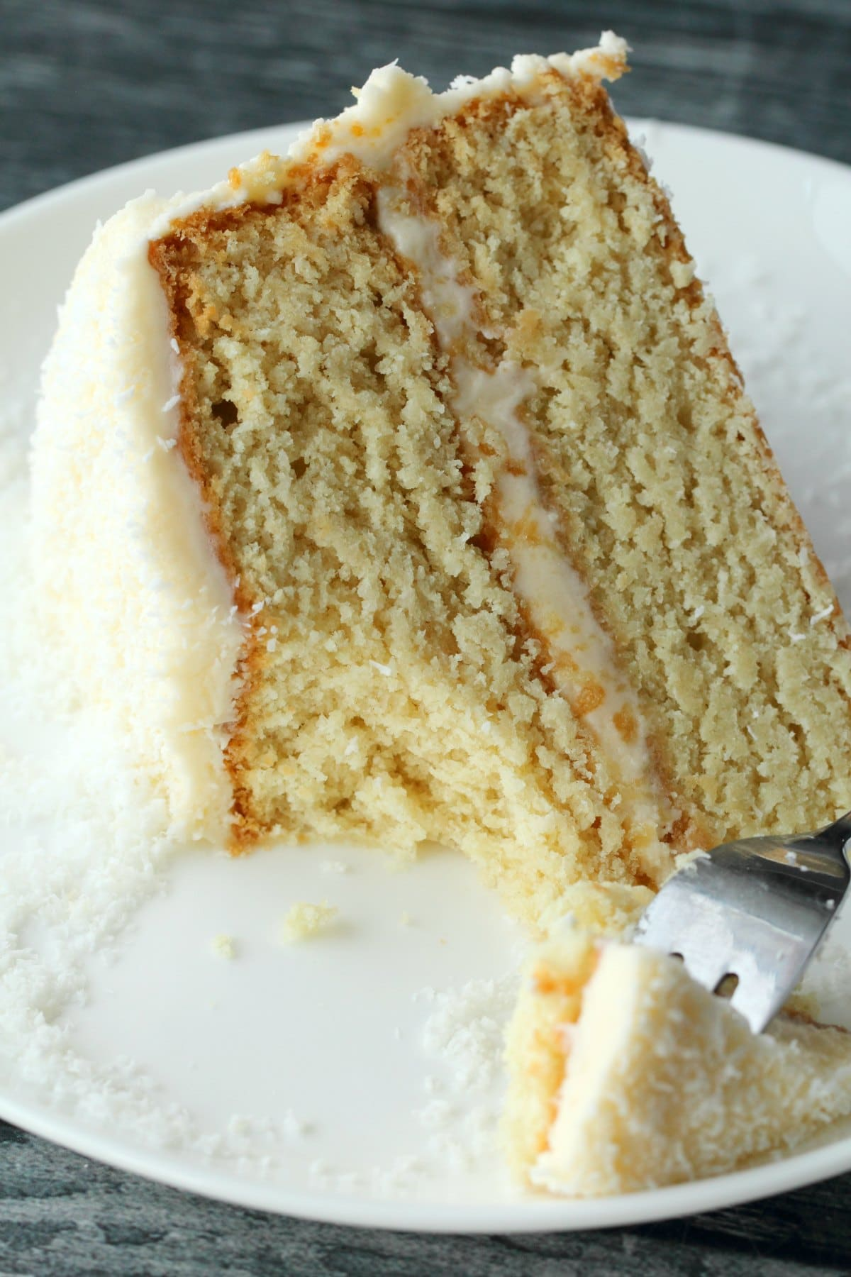 A slice of vegan coconut cake on a white plate with a cake fork.