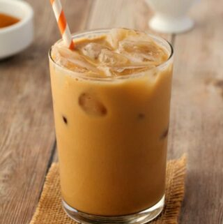 Vegan iced coffee in a glass with a straw.