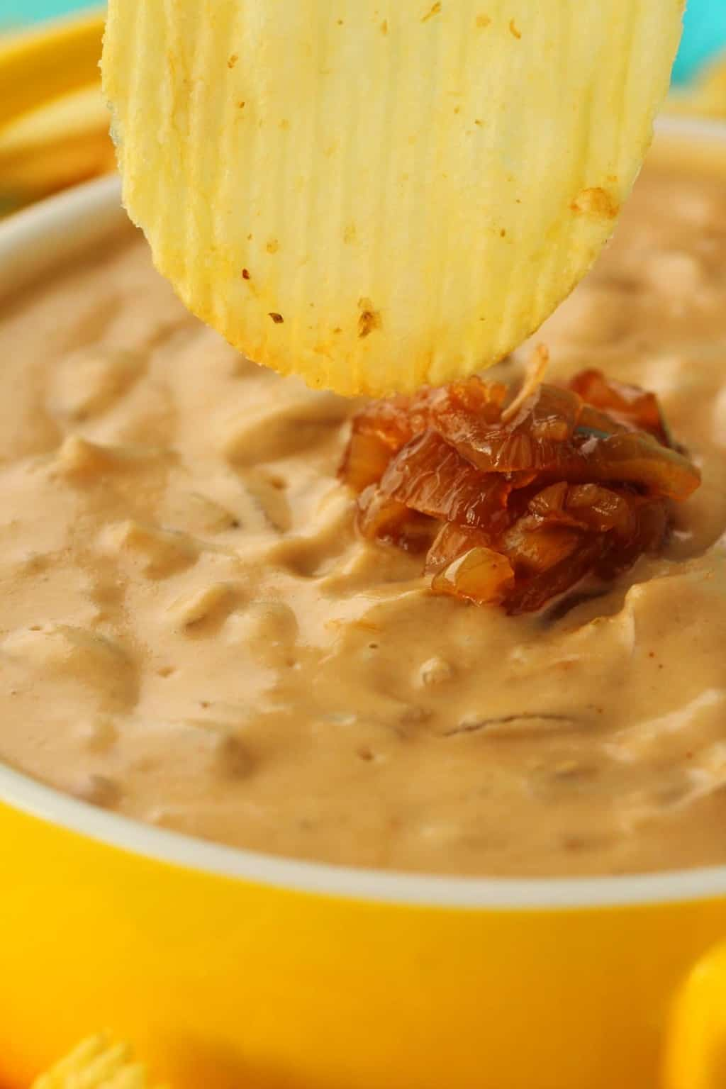 A chip dipping into a bowl of vegan onion dip.