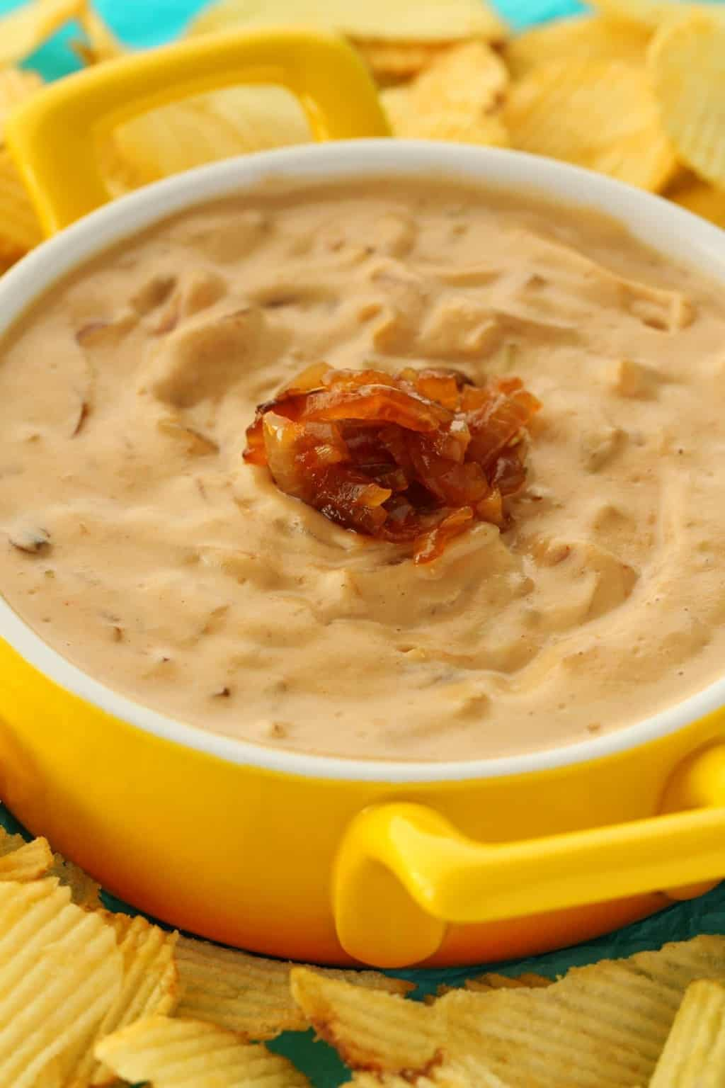 Vegan Onion Dip in a yellow and white serving dish surrounded by chips.